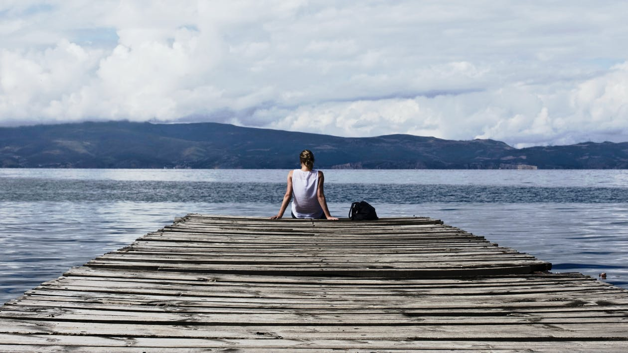 Person Sitting on Brown Wooden Dock Under Cloudy Blue Sky