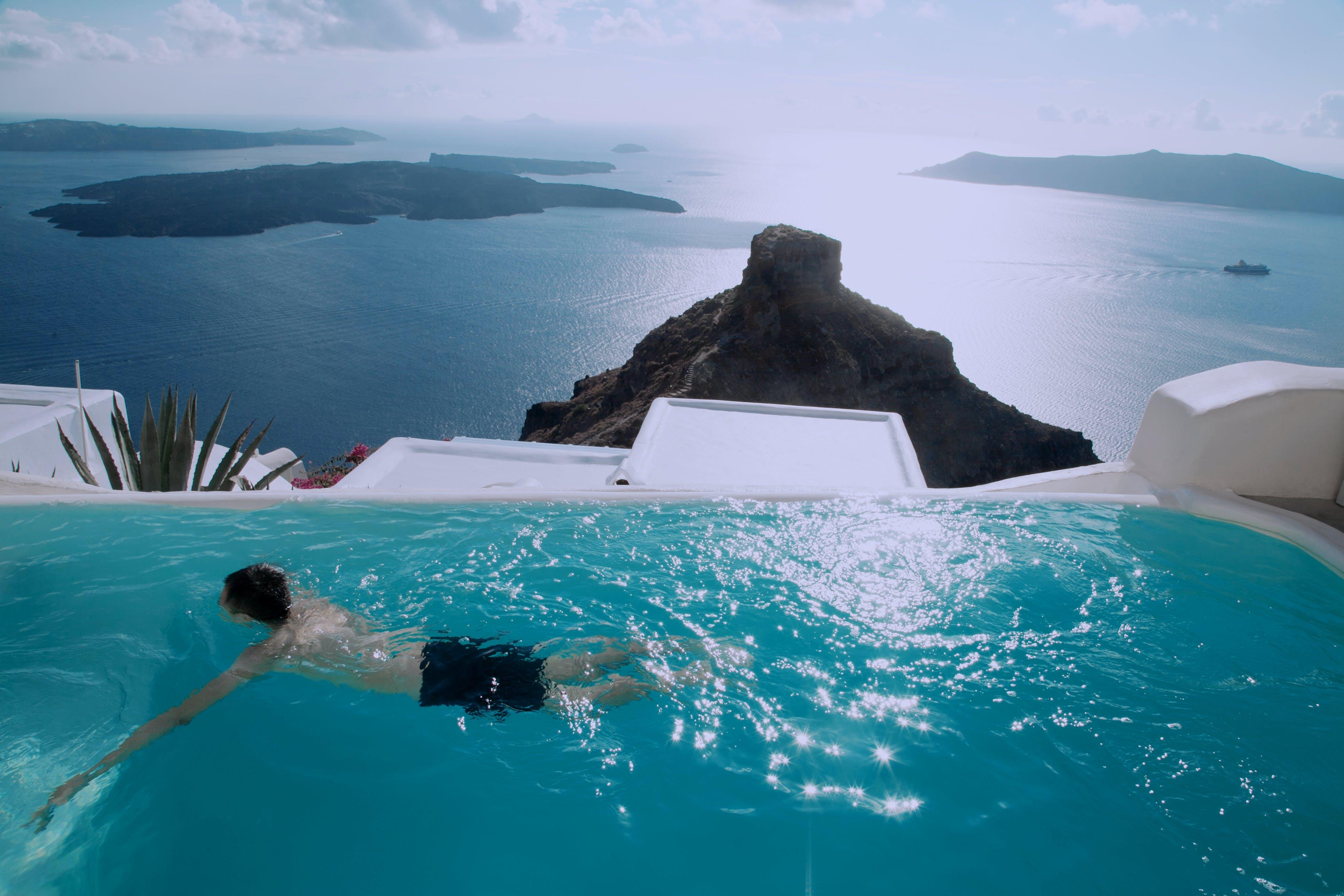 Man Wearing Black Shorts Swimming in Infinity Pool