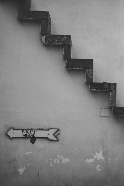 Grayscale Photo of Exit Signage Under Brown Stairs