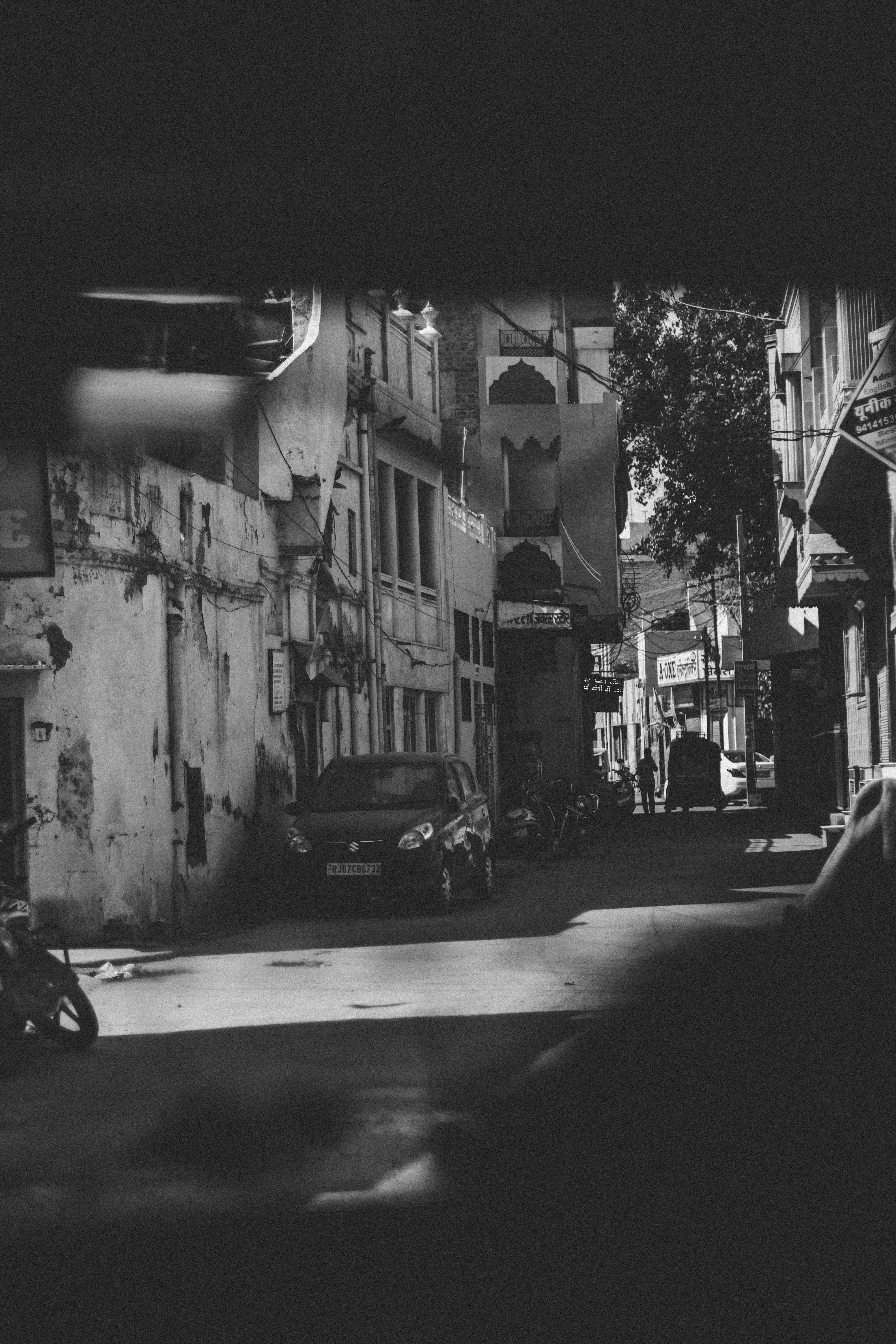 Grayscale Photography of Car and Motorcycle Beside Building