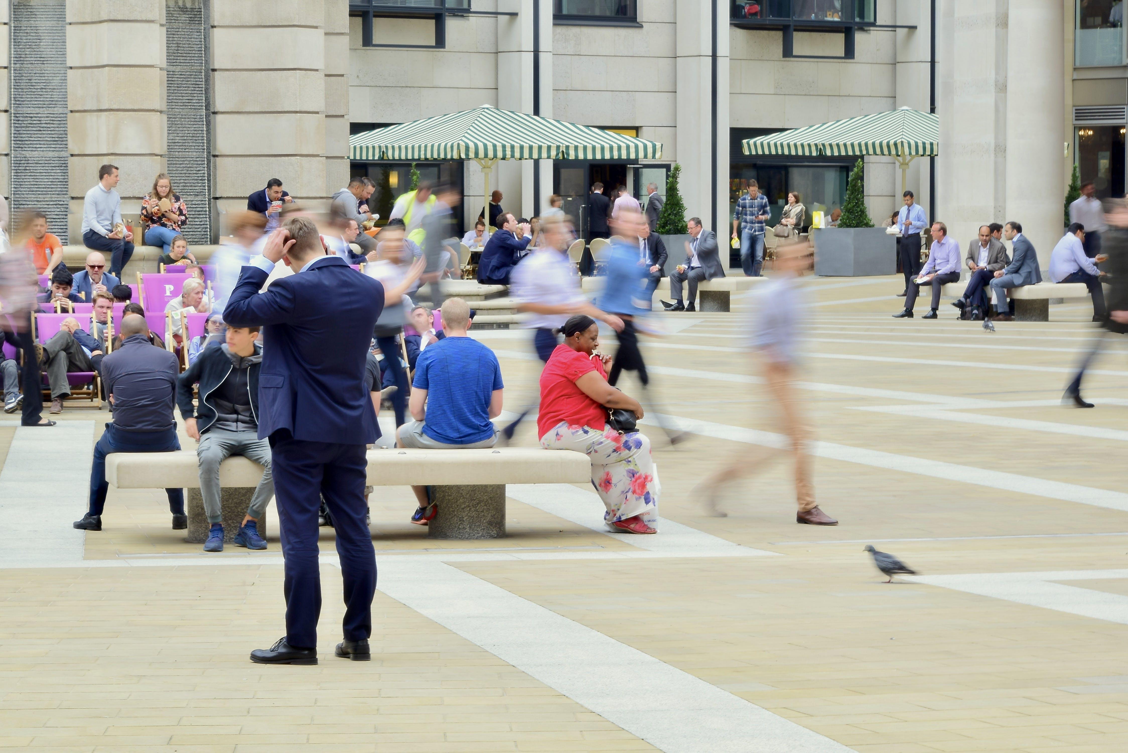 Man Wearing Blue Suit on Beige Ground Near Building