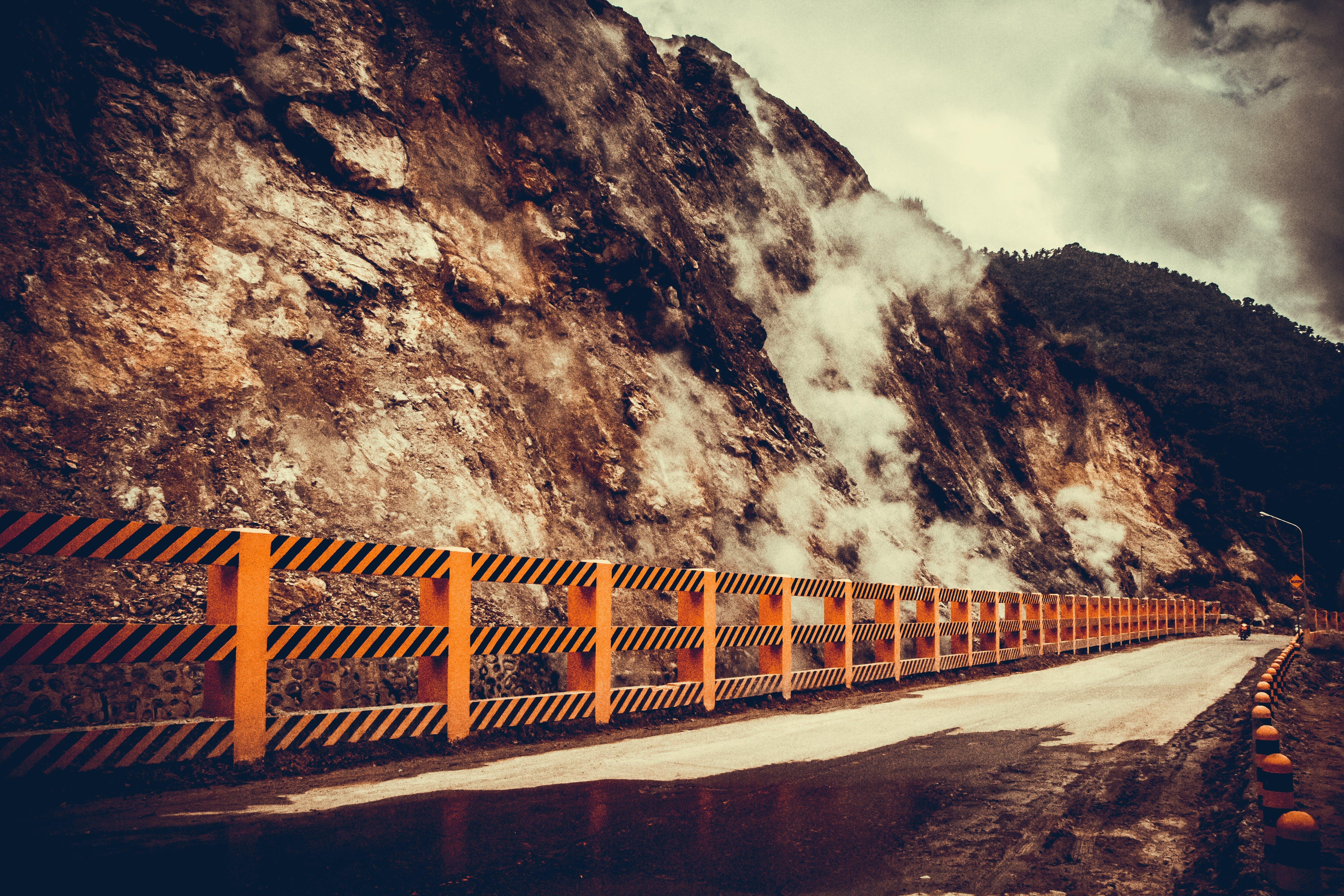 Concrete Road Near Mountain at Daytime