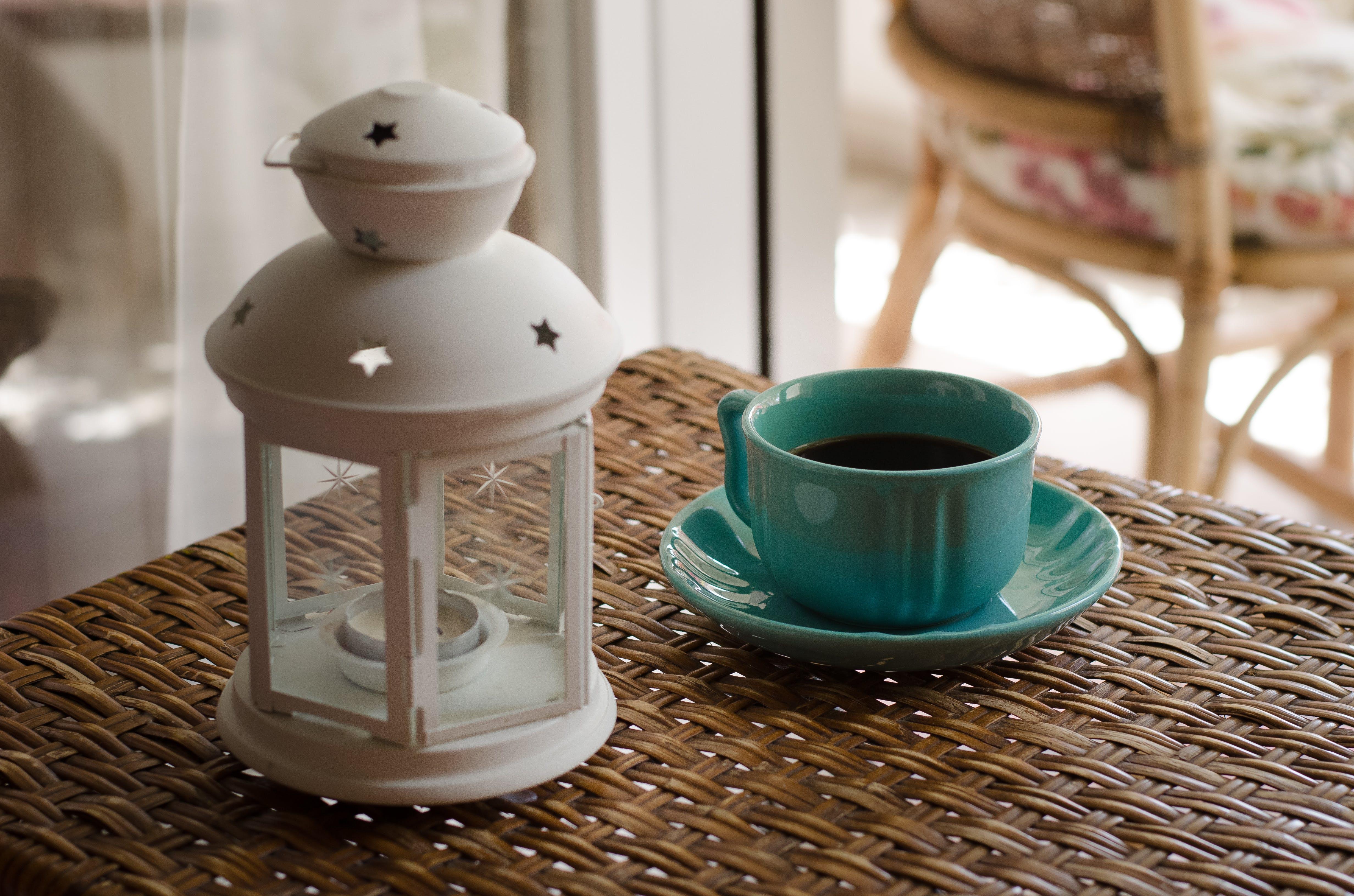 White Candle Lantern Beside of Blue Ceramic Coffee Mug on Wicker Table