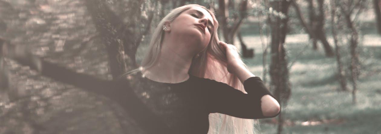 Woman Wearing Black Long-sleeved Shirt Near Trees