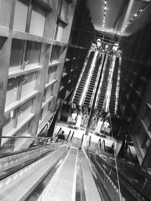 Grey Scale Photo of Escalator