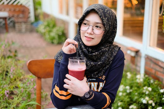 Woman Holding Cup of Red Juice