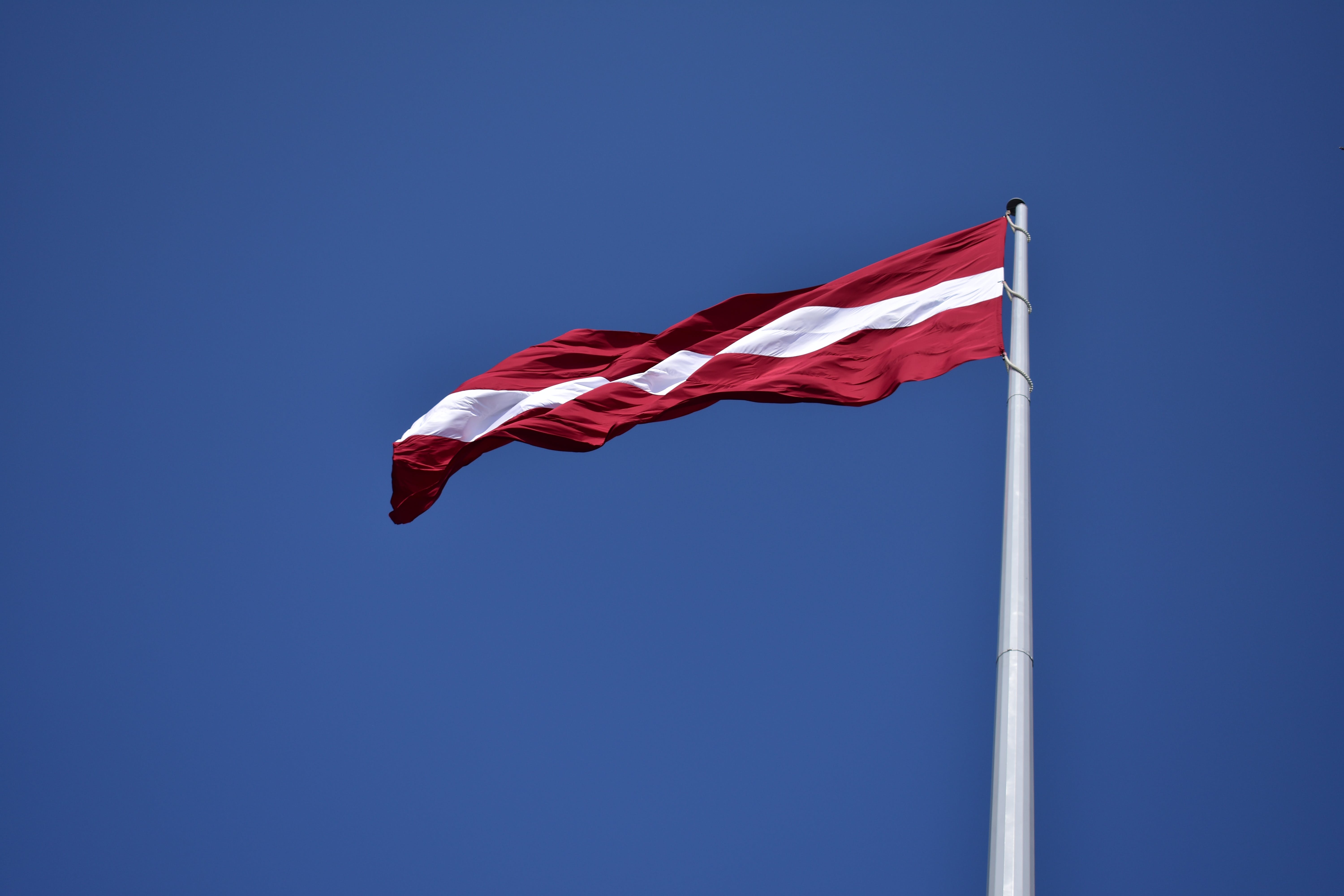 Red and White State Flag Waving Under Blue Sky at Daytime