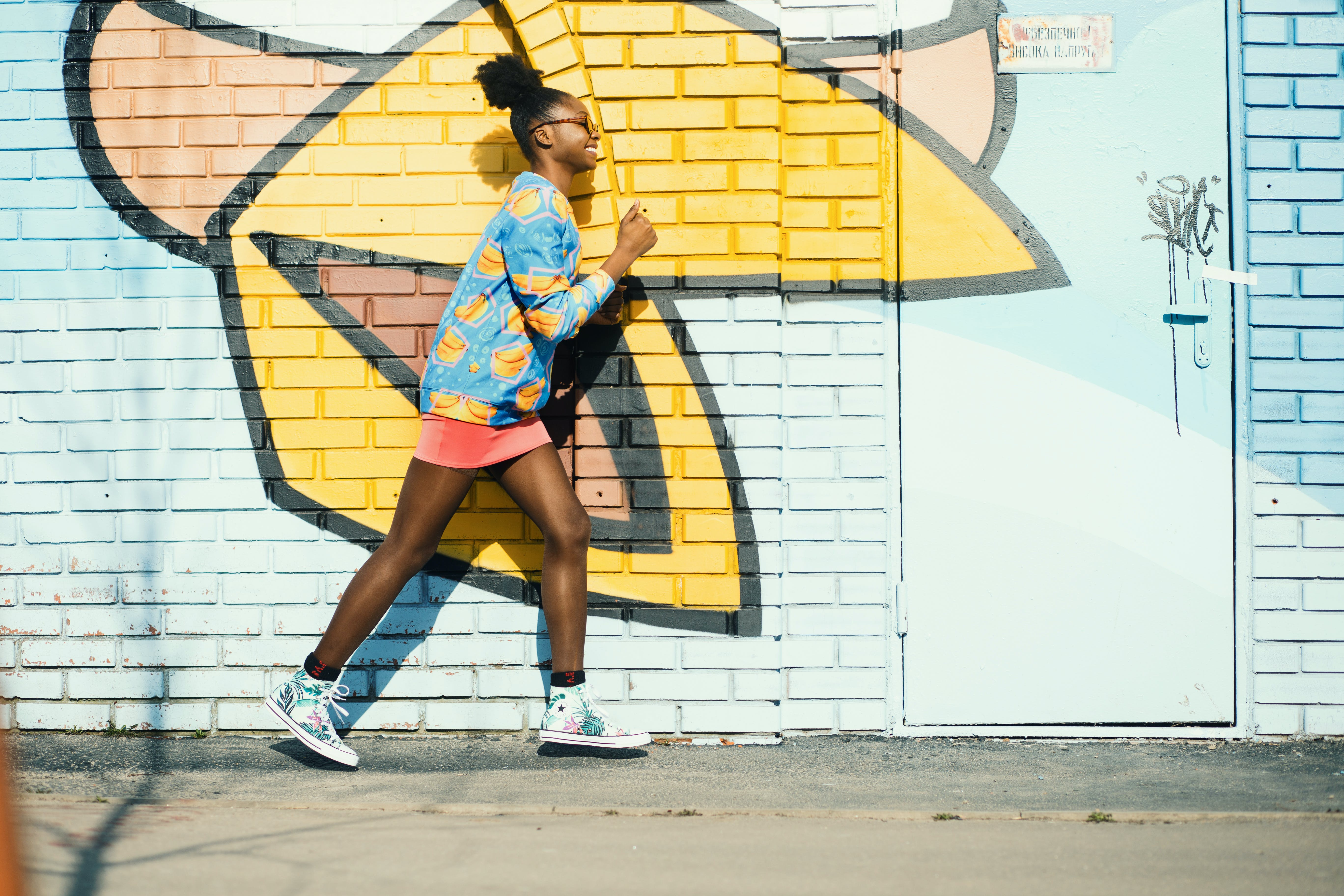 Woman Wearing Blue and Yellow Long-sleeved Shirt Walking Near White and Yellow Painted Wall