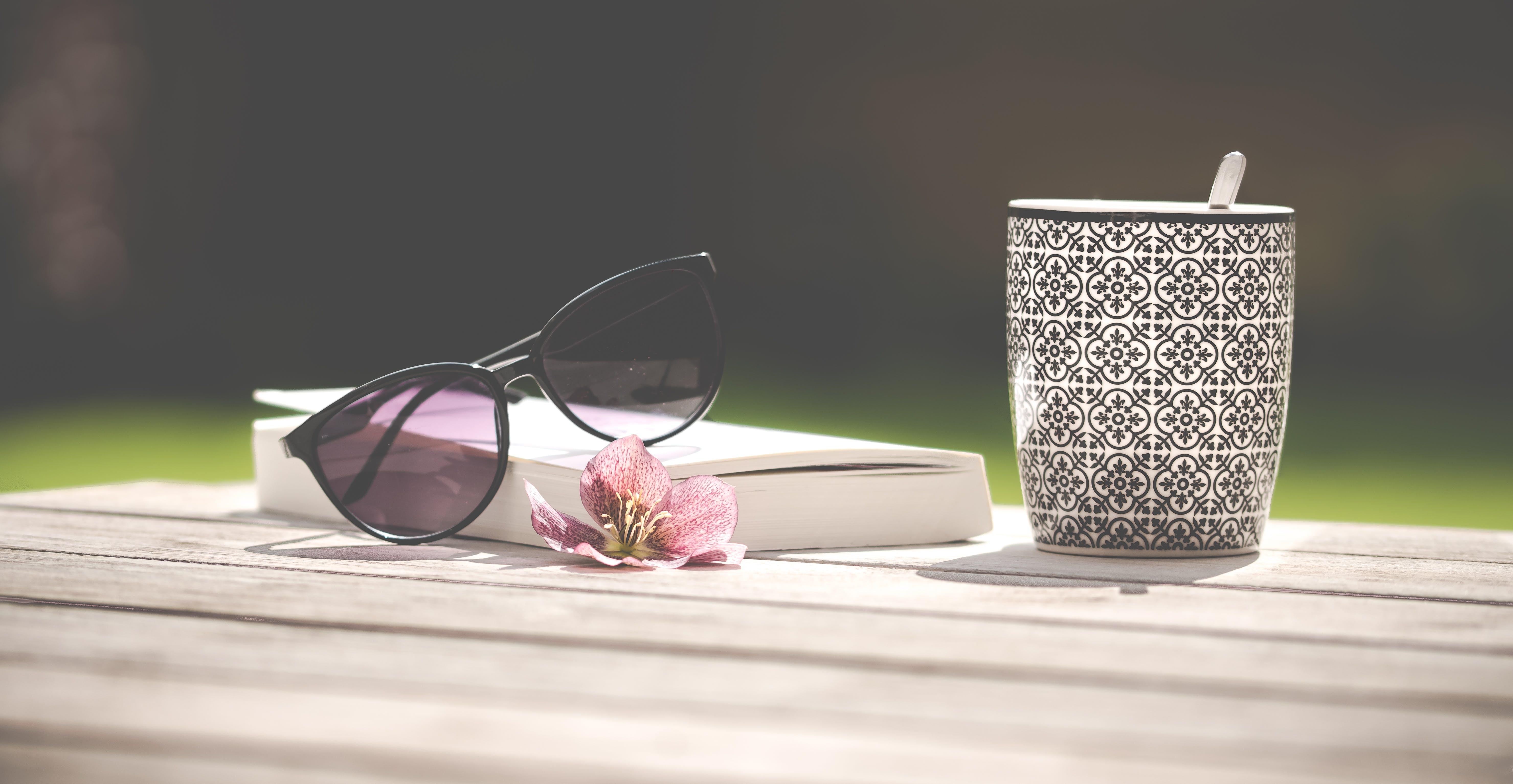 Photo of Black Sunglasses Beside Ceramic Mug