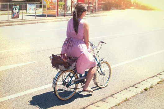 Woman in Purple Dress Riding on City Bicycle on Road