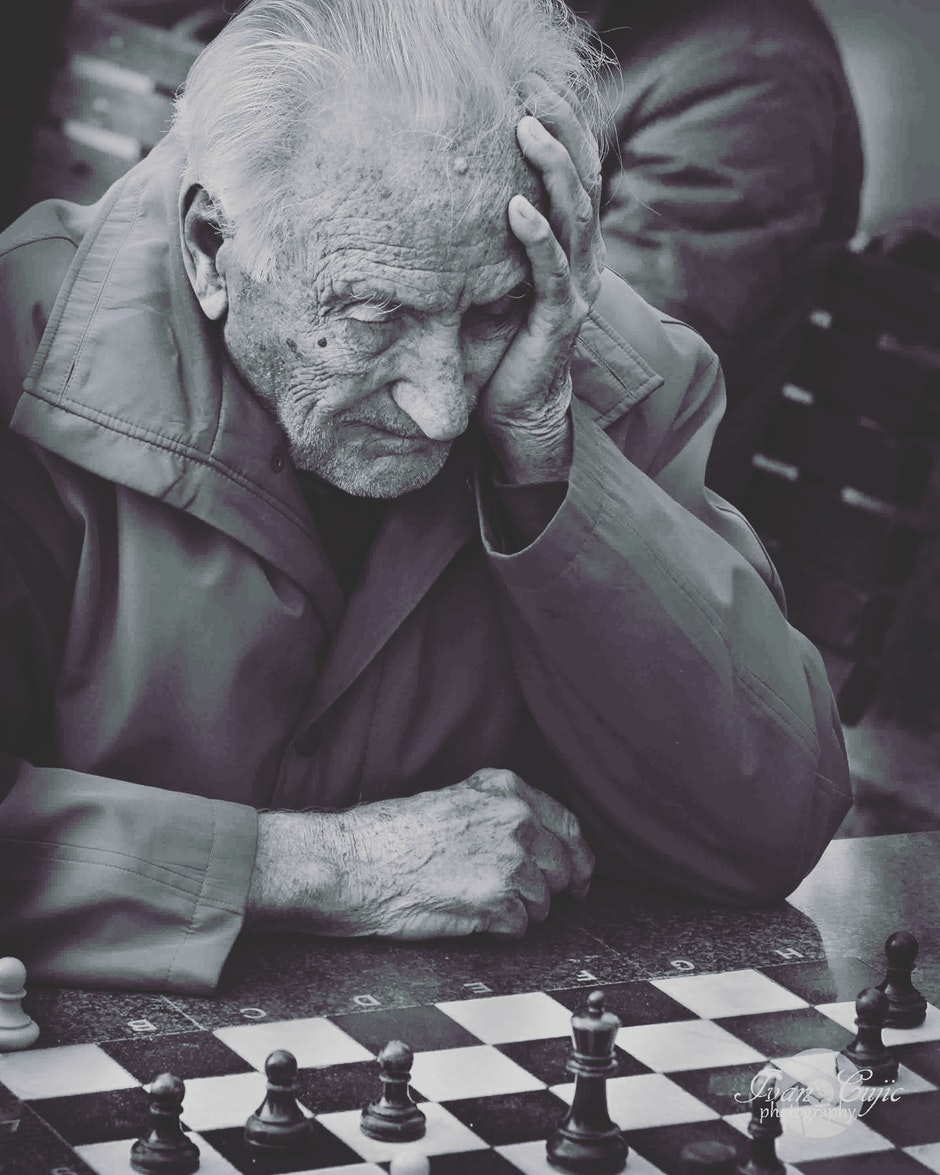 Grayscale Photo of Man Playing Chess