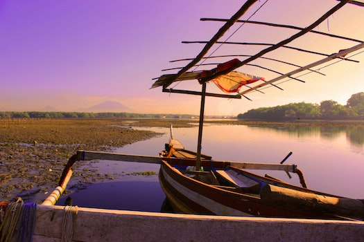White and Brown Rowboat on Calm Body of Water during Sunset