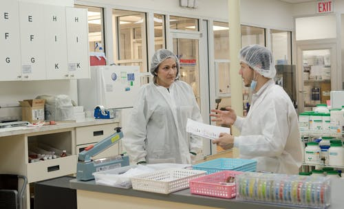 Concentrated laboratory workers wearing white robes and hats standing with papers in contemporary chemical room and discussing results of scientific research