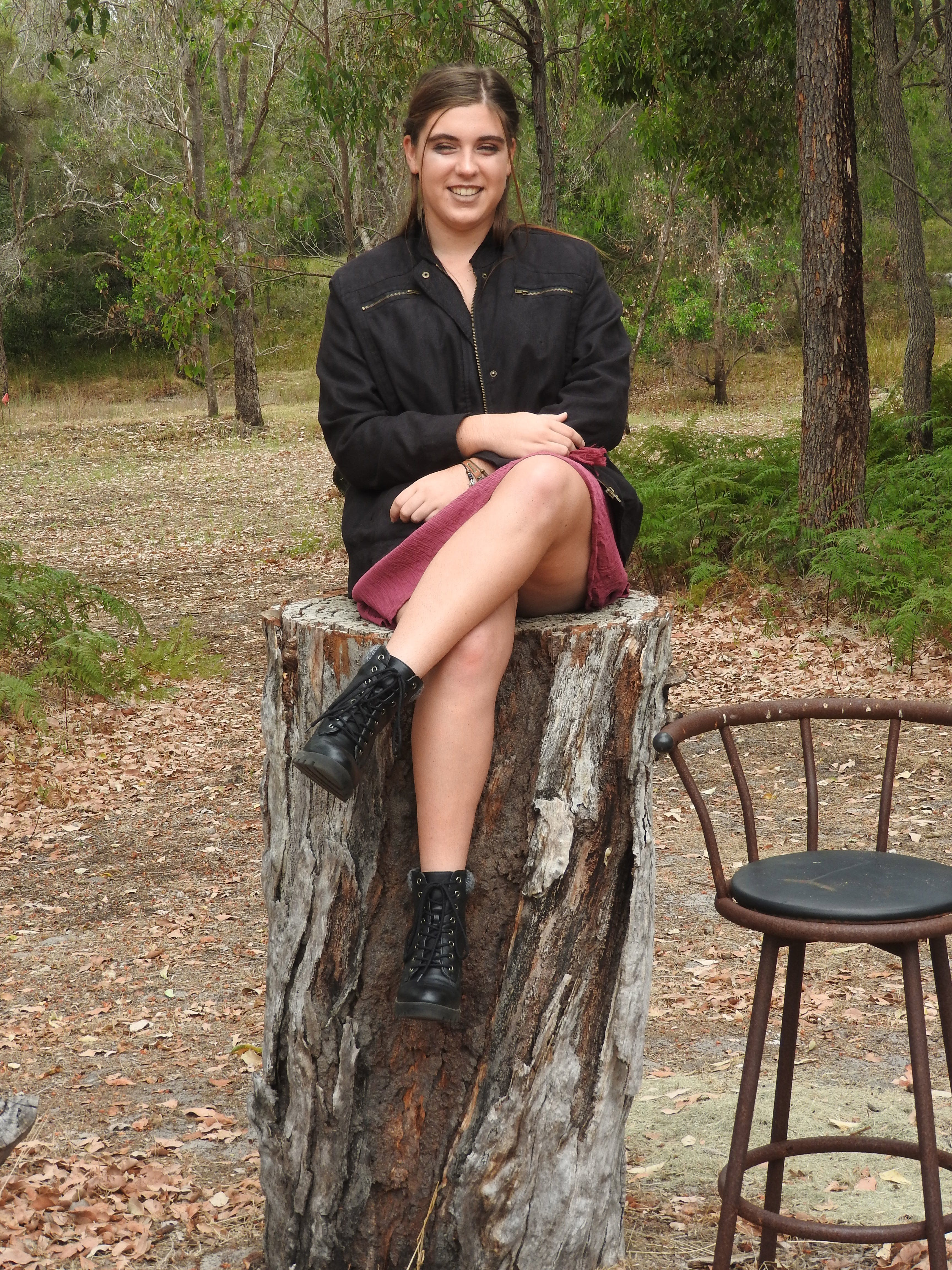 Woman Wearing Black Jacket Sitting on Tree Log Near Bar Stool