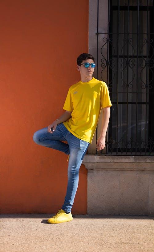 Hombre Vestido Con Camiseta Amarilla Con Cuello Circular Y Vaqueros Azules