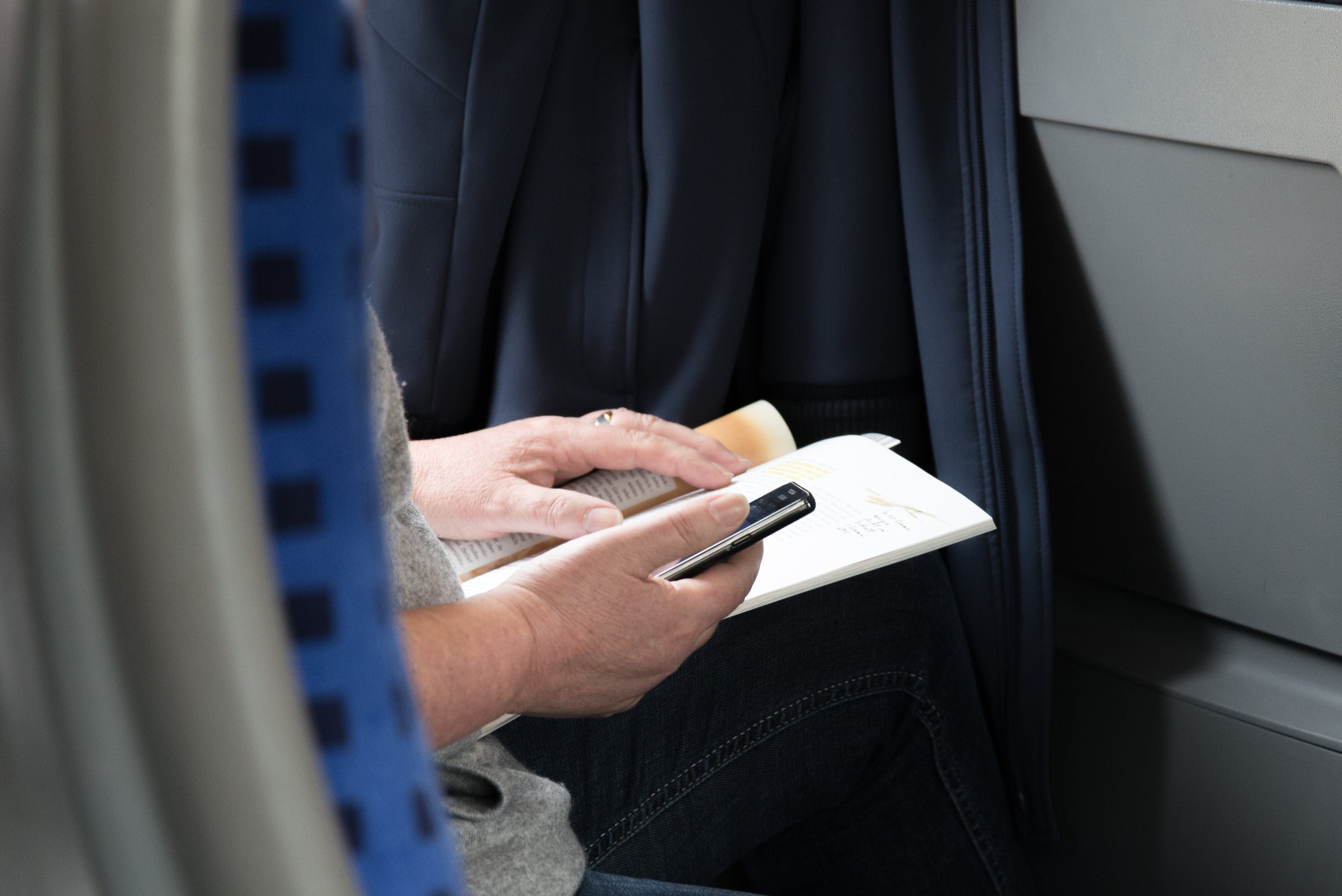 Person in Gray Shirt Holding Black Smartphone and Brown Book