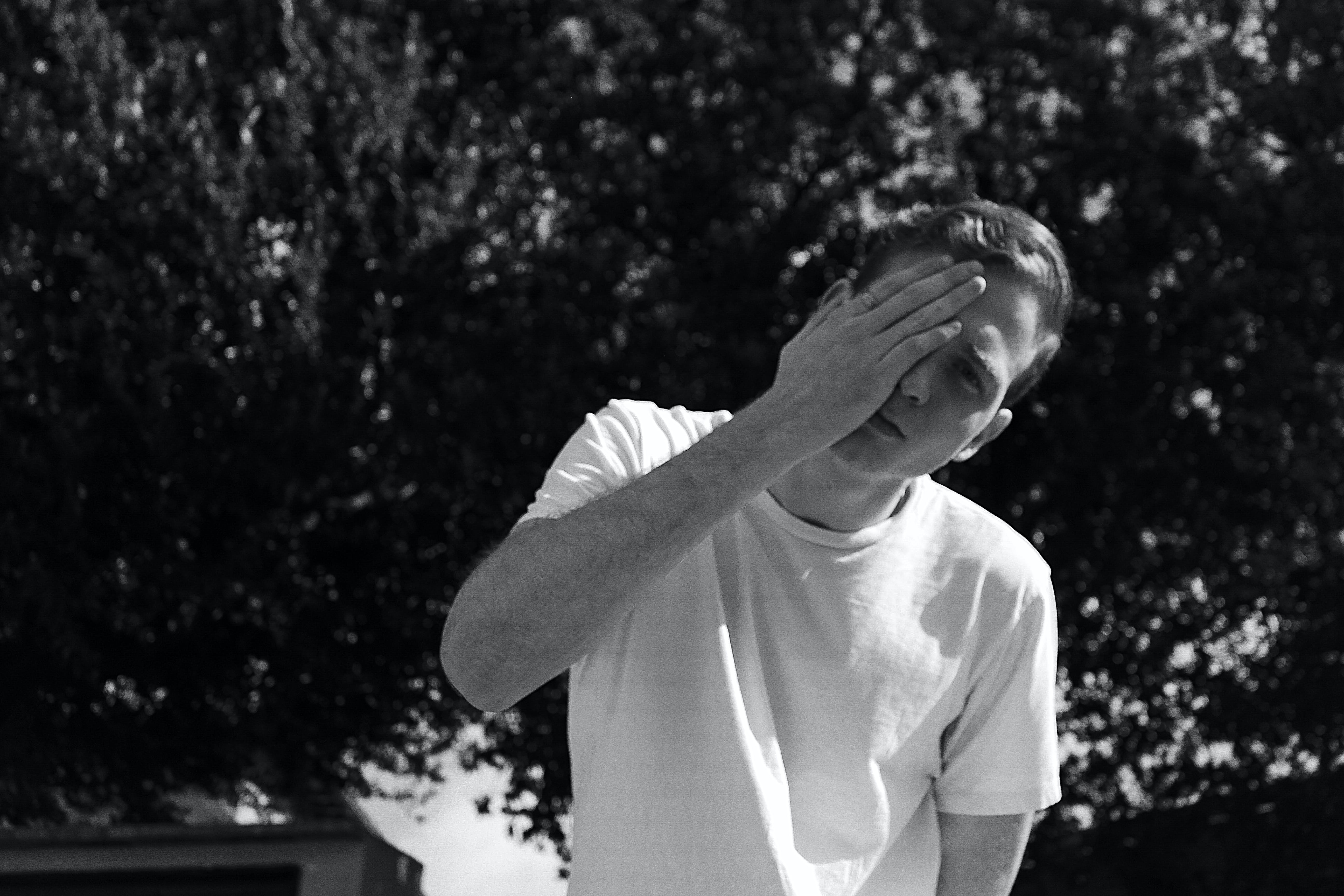 Grayscale Photo of Man Wearing White Crew-neck Shrit