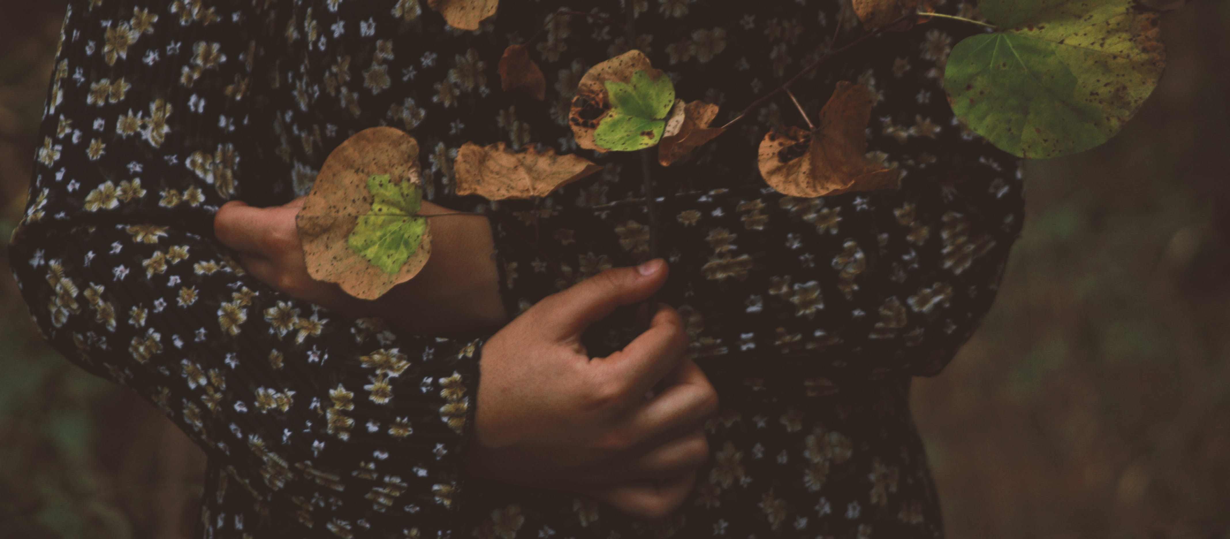 Photo of Person Wearing Black and White Floral Long-sleeved Shirt With Leaves All over in Top
