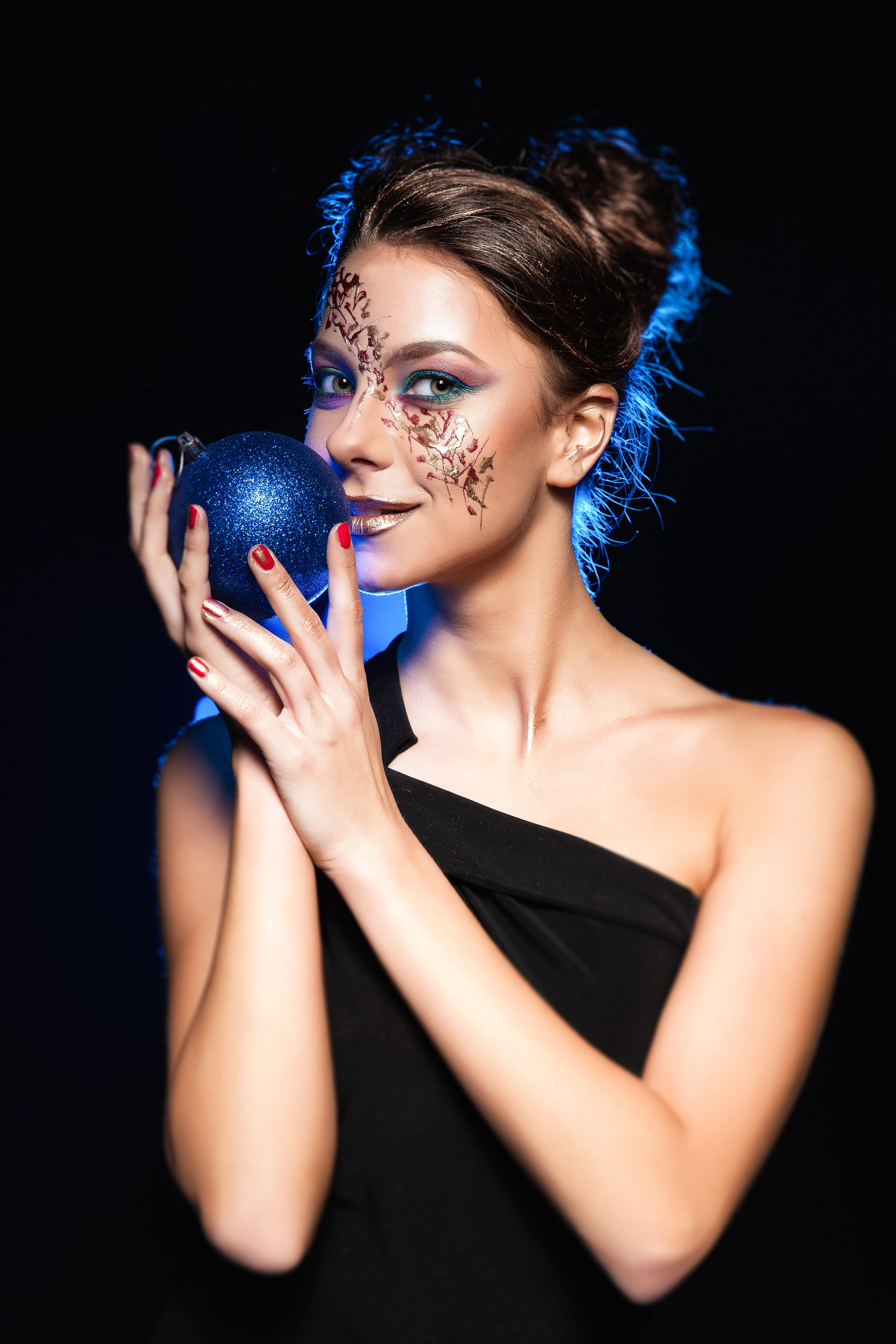 Woman Wearing Black One Shoulder Top Holding Bauble