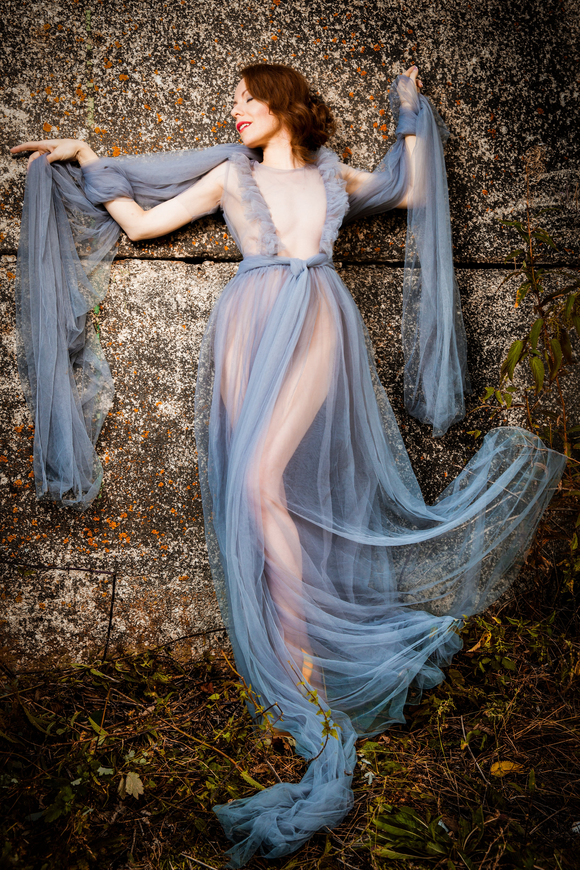 Woman Wearing Mesh Blue Dress Lying on Gray Concrete Floor