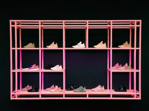 다양한 색상과 스타일의 신발이 달린 핑크색 신발장
