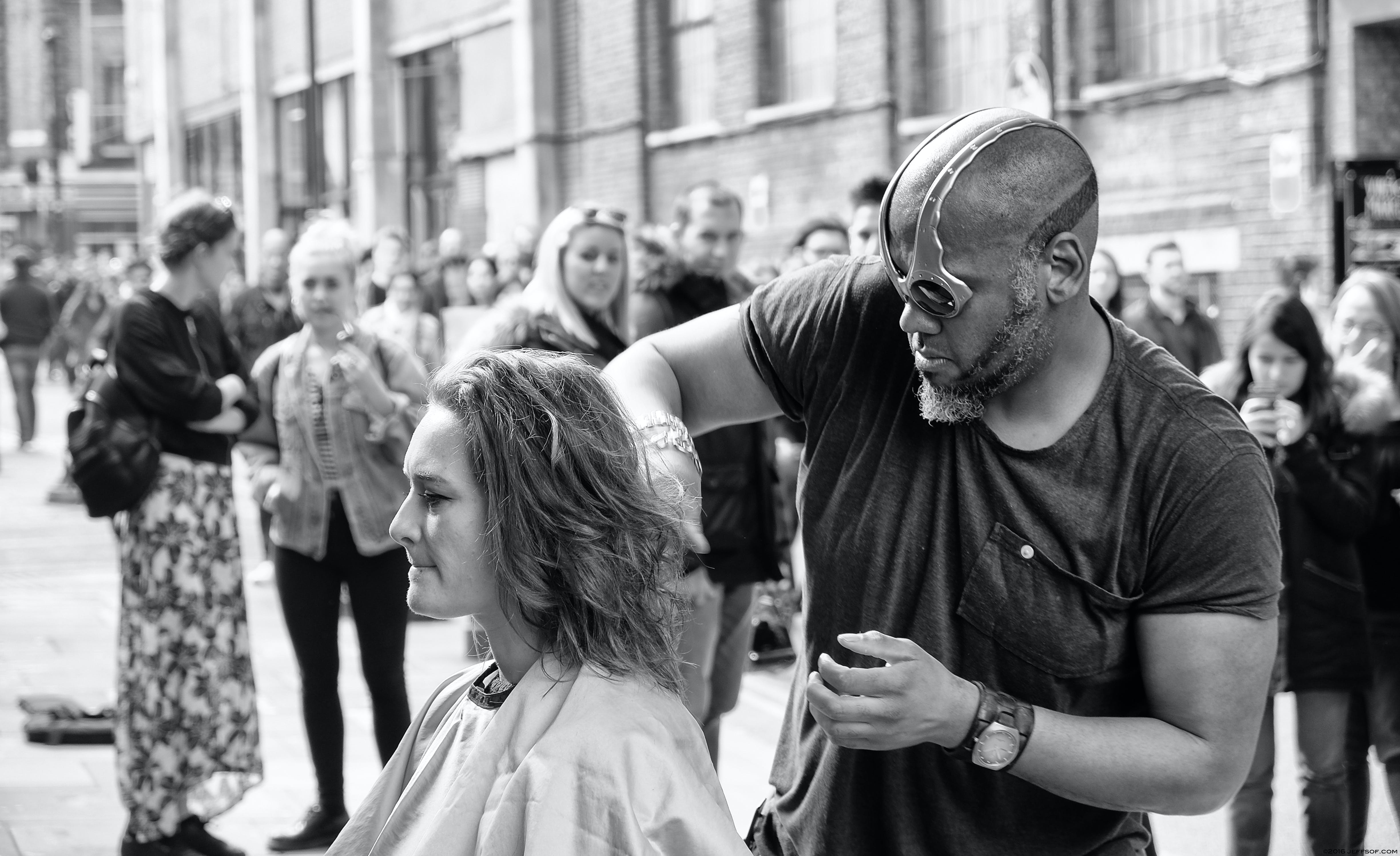 Grayscale Photography of Man Cutting Hair of Woman Surrounded With People