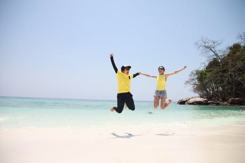 Woman in Blue Denim Mini Short Smiling While Holding Another Person in a Jump Shot Photo at Seashore during Daytime