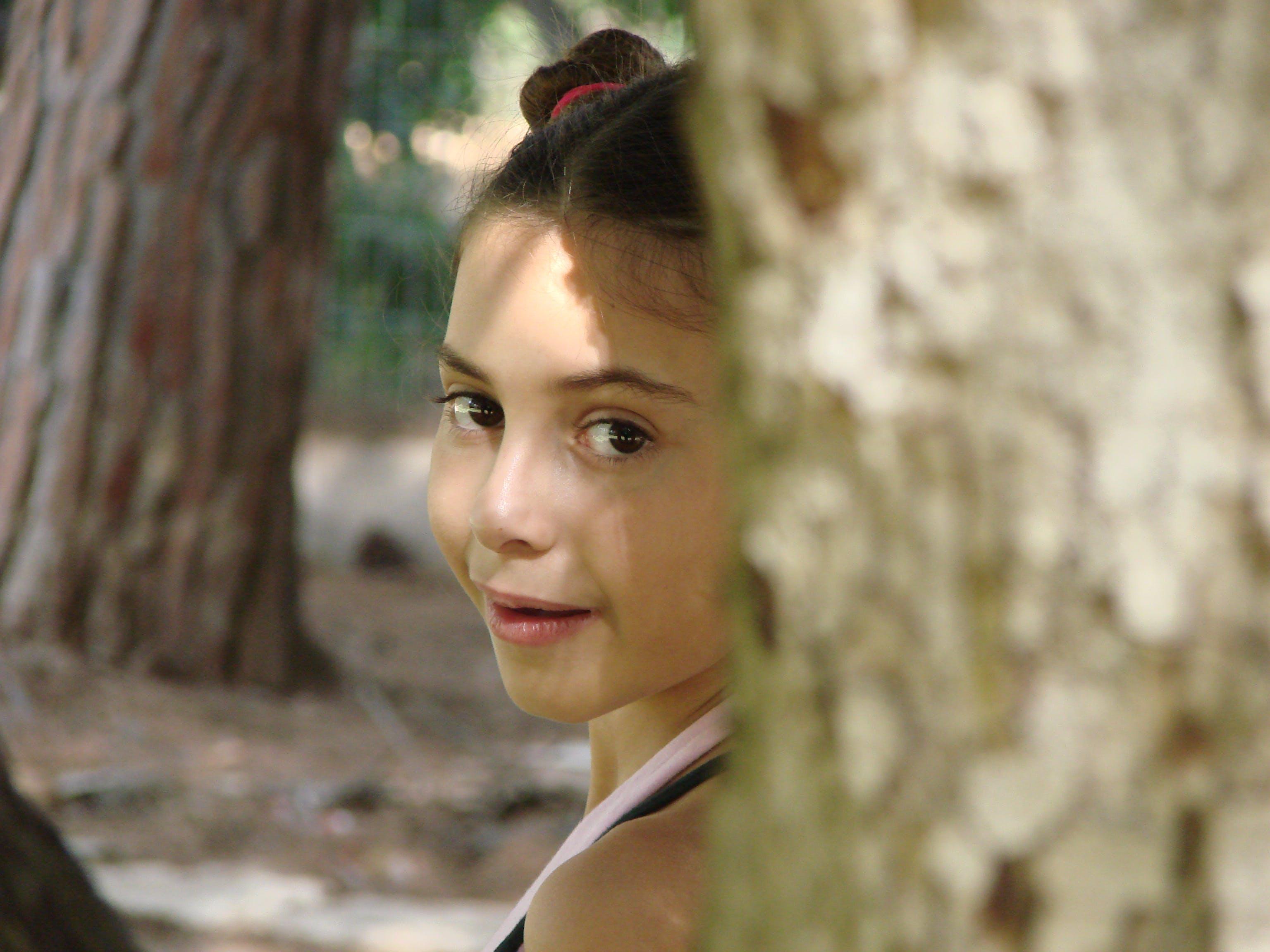 나무 뒤에 어린 소녀의 무료 스톡 사진
