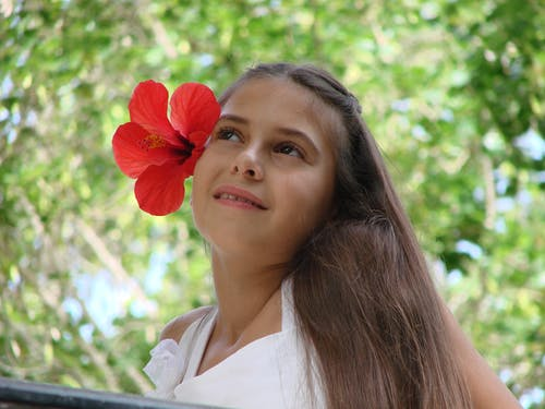 คลังภาพถ่ายฟรี ของ ชุดเดรสสีขาว, เด็กผู้หญิงที่มีดอกไม้สีแดงในผมของเธอ