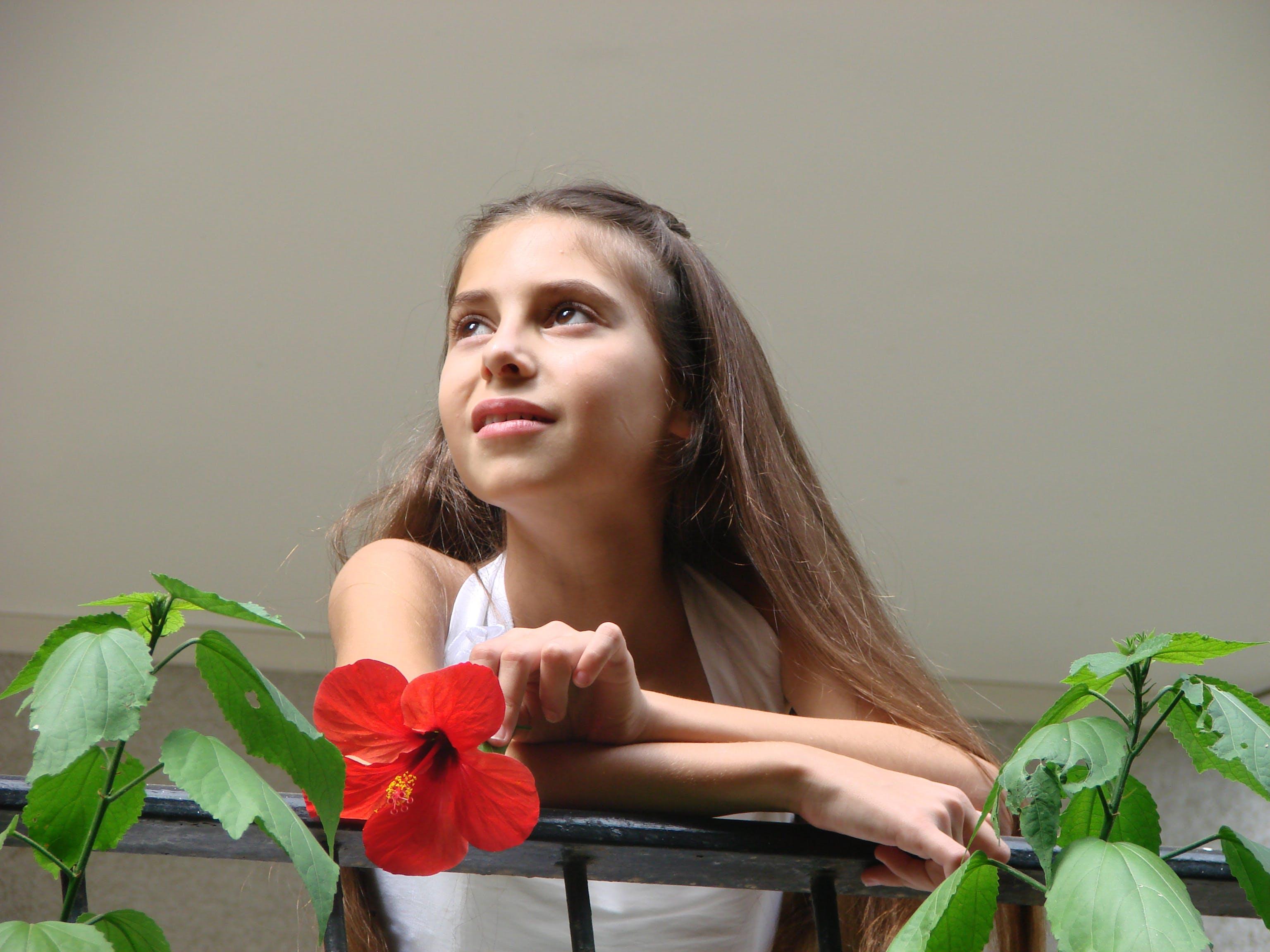 발코니에 붉은 꽃을 들고 어린 소녀, 하얀 드레스의 무료 스톡 사진