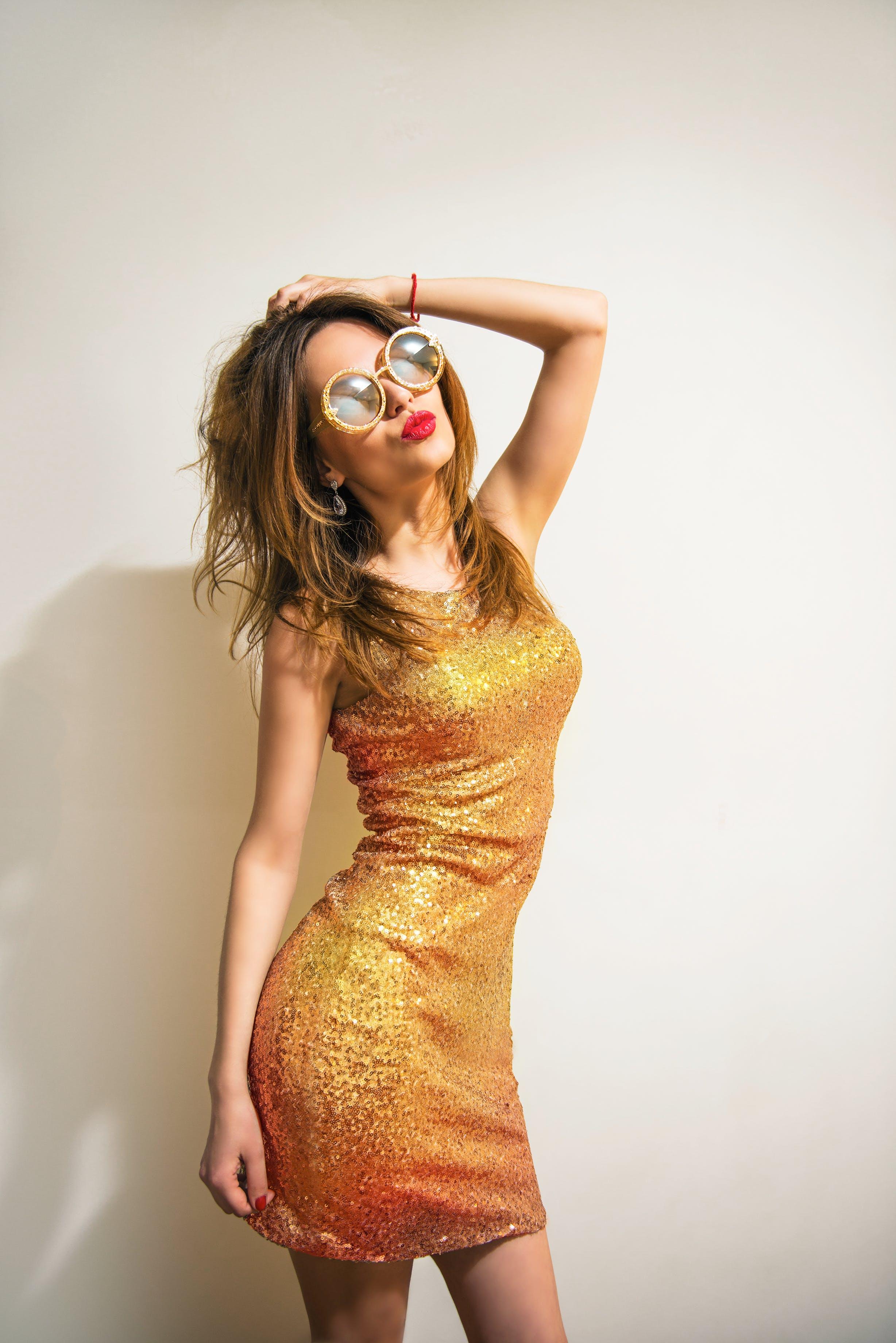Woman Wearing Gold Sleeveless Mini Dress