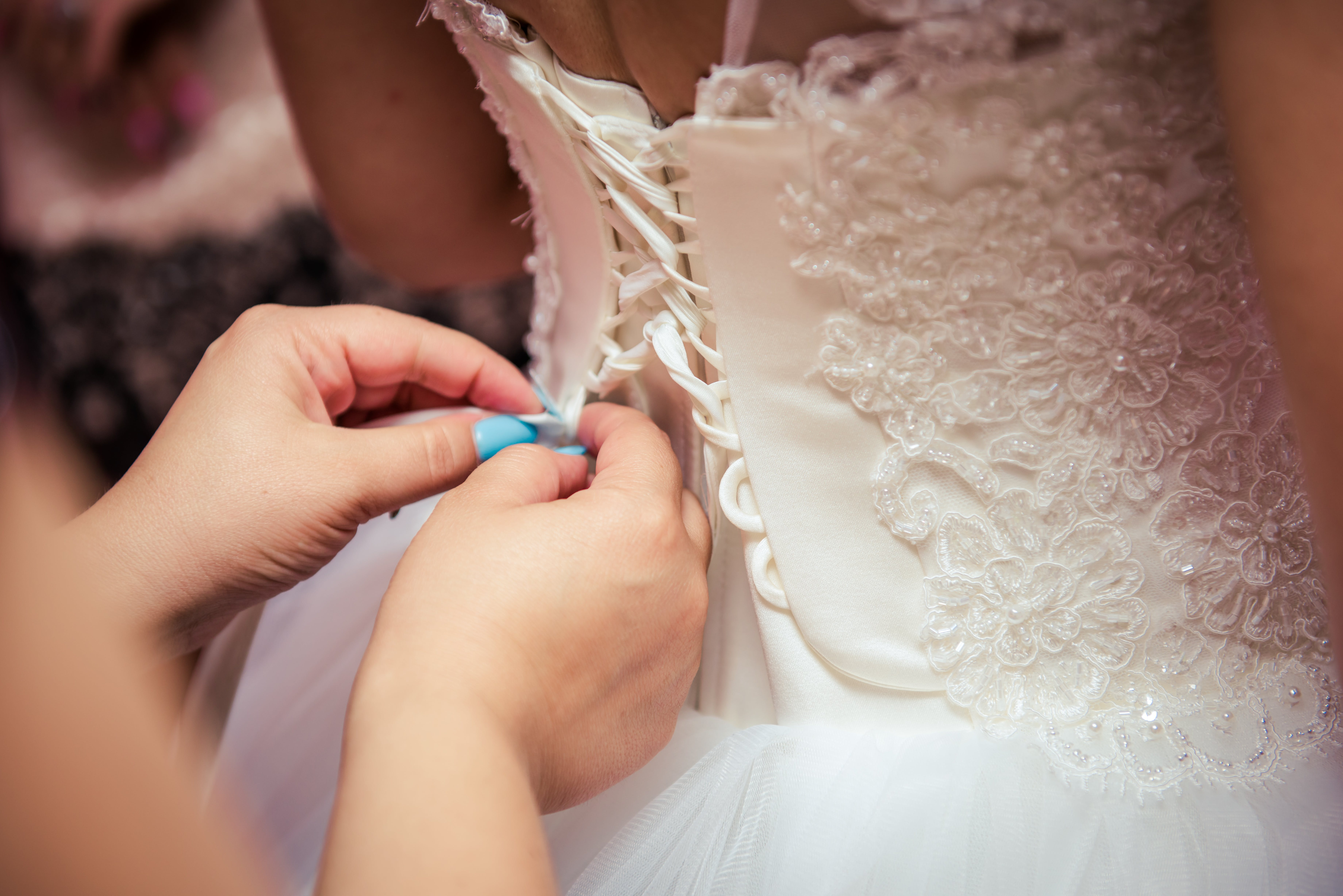 Photo of Woman Fixing the Wedding Gown