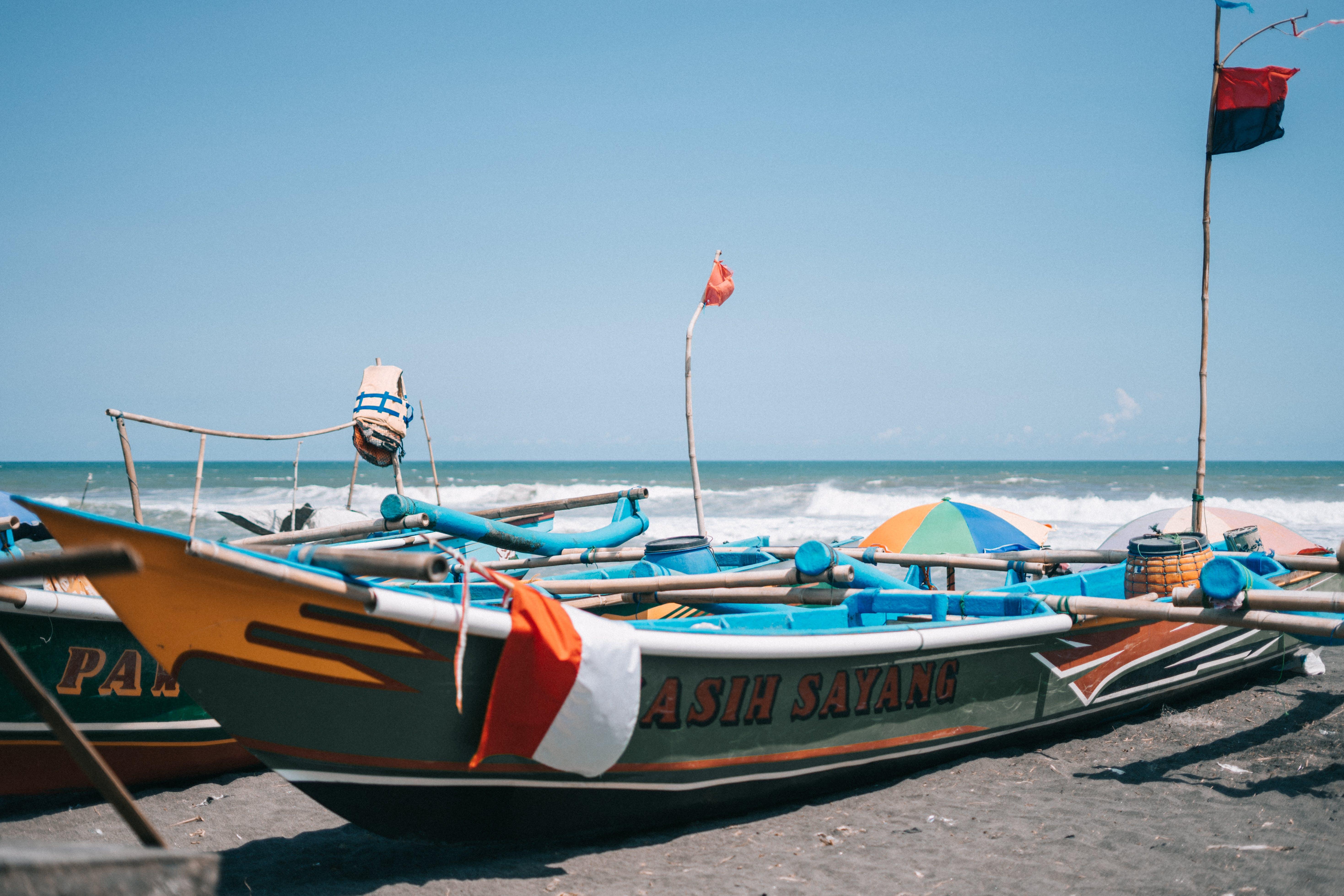 Green and Orange Boat Near Seashore