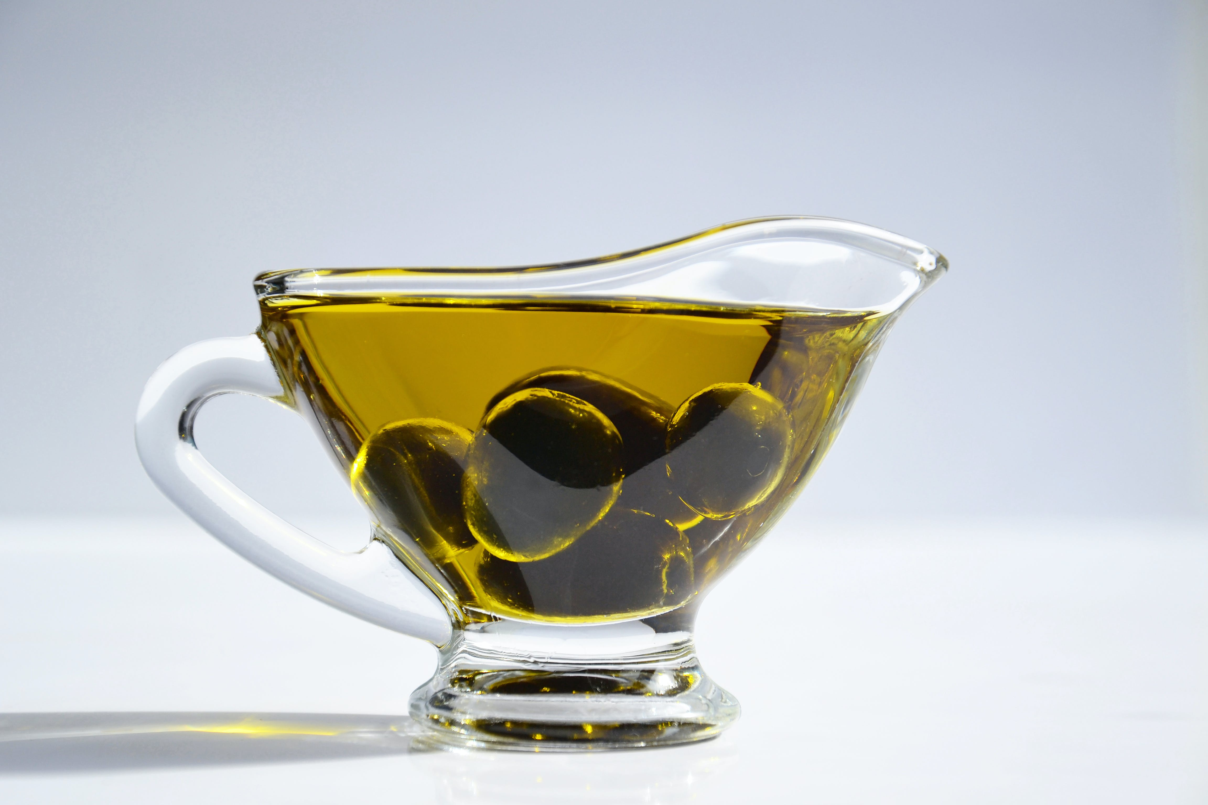 Photo of Olives on Cup of Olive Oil