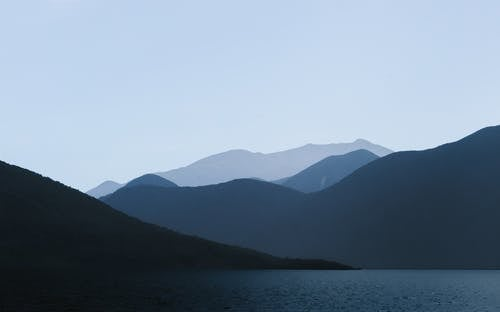 Photo of Mountains Near Body of Water