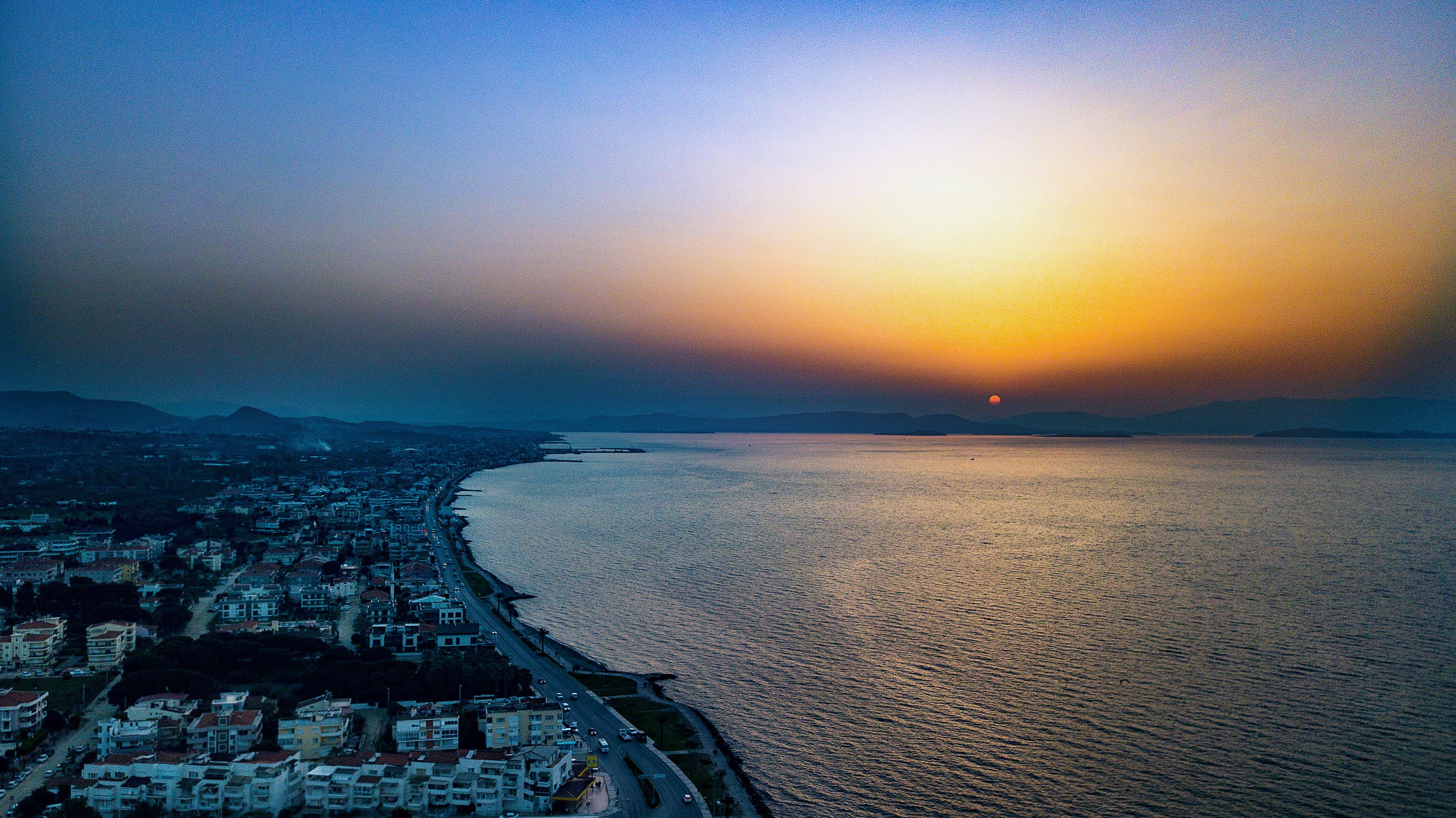 Bird's Eye View of City Near Ocean During Dawn