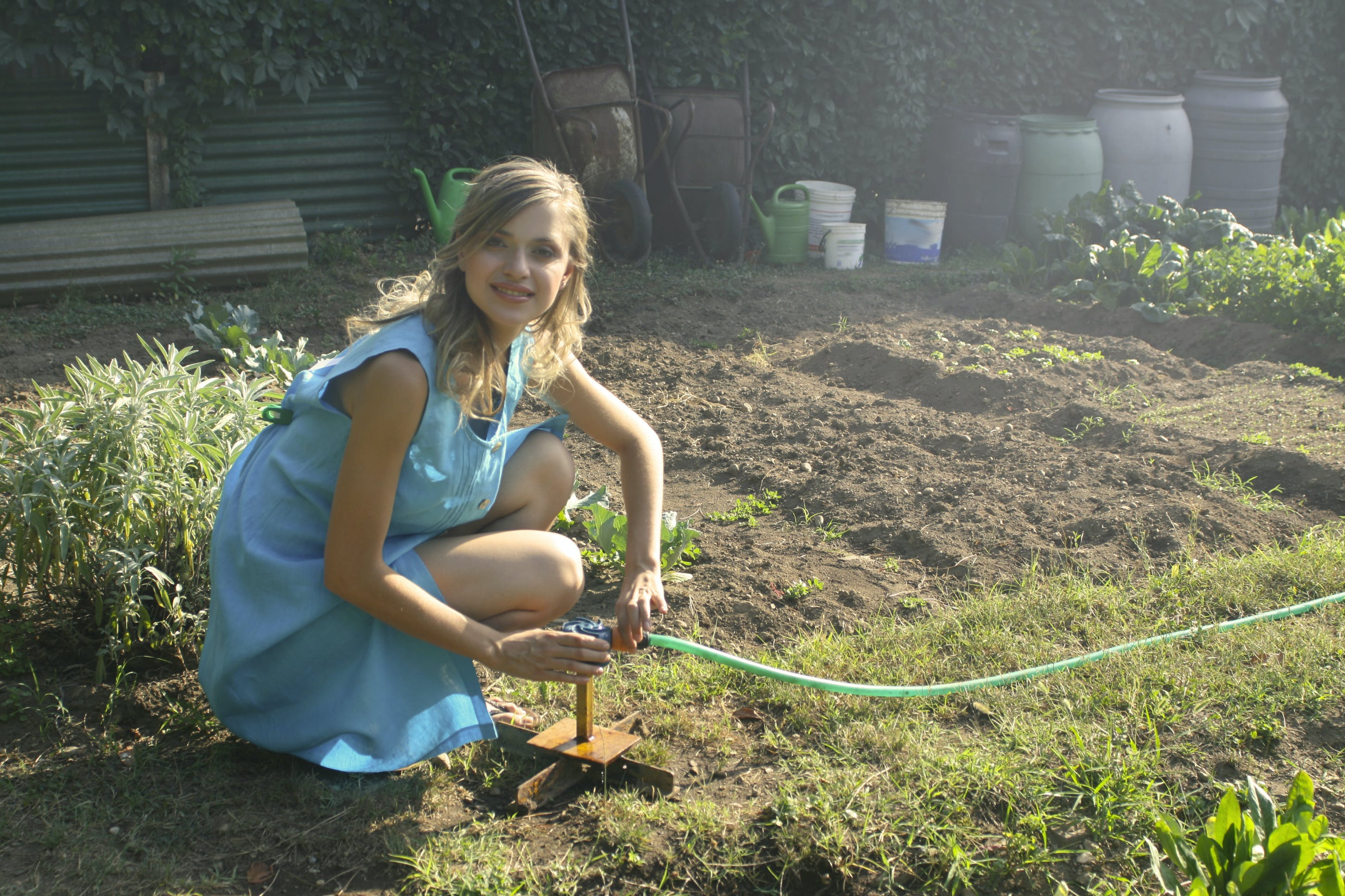 Photo Woman Holding Green Garden Hose