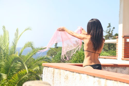 Photo of Woman in Black Bikini Holding Pink Scarf in Balcony
