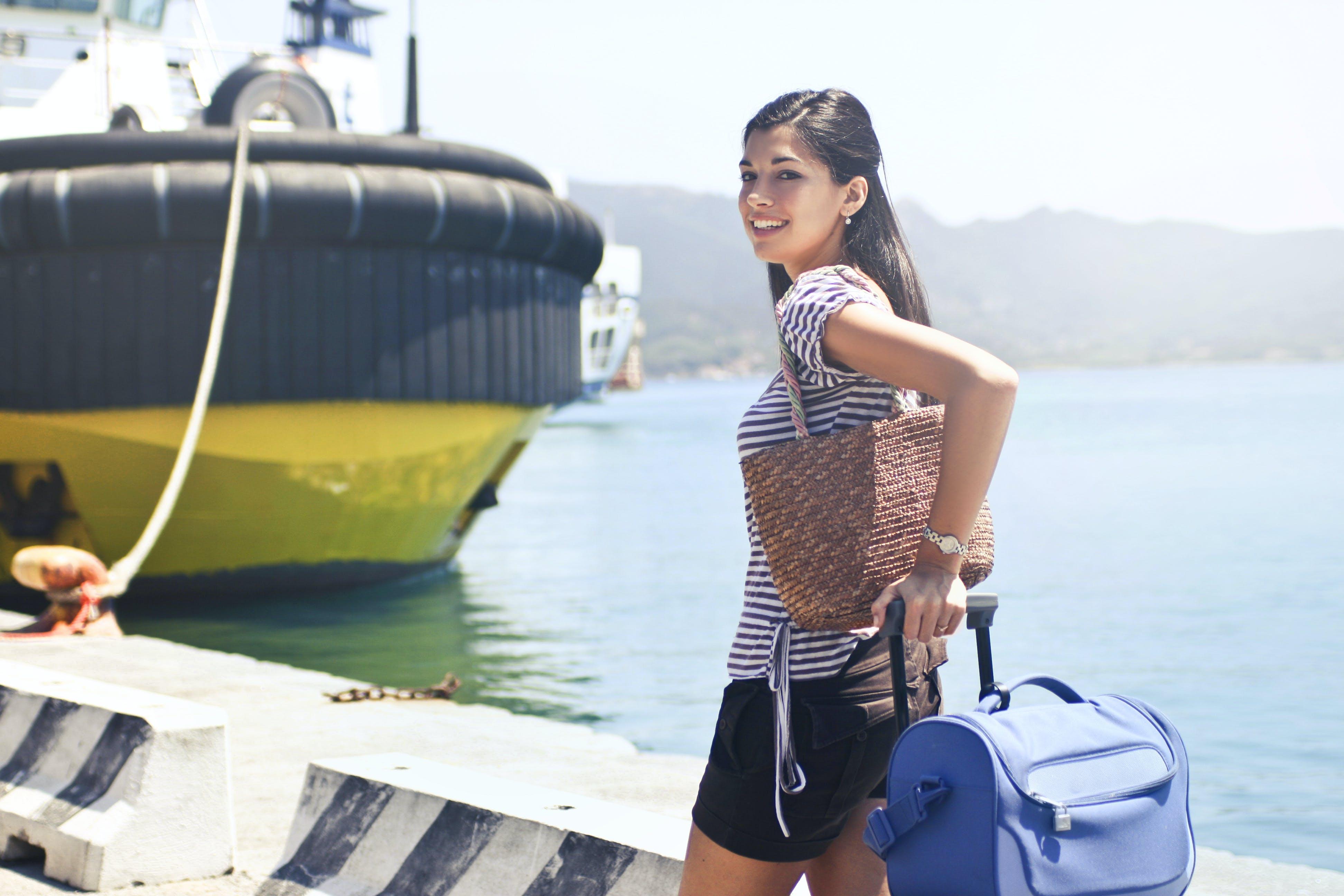 Woman Standing on Dock Near Ship Holding Luggage and Carrying Handbag