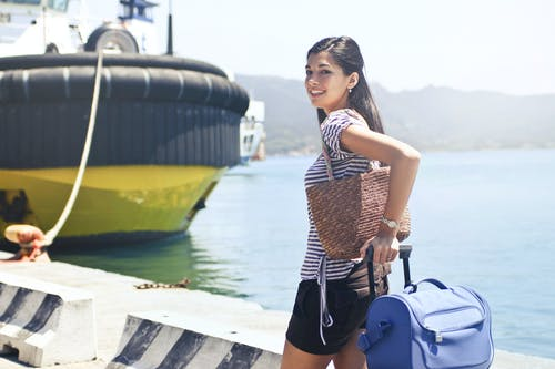 Woman Standing on Dock Near Ship Holding Luggage and Carrying Handbag