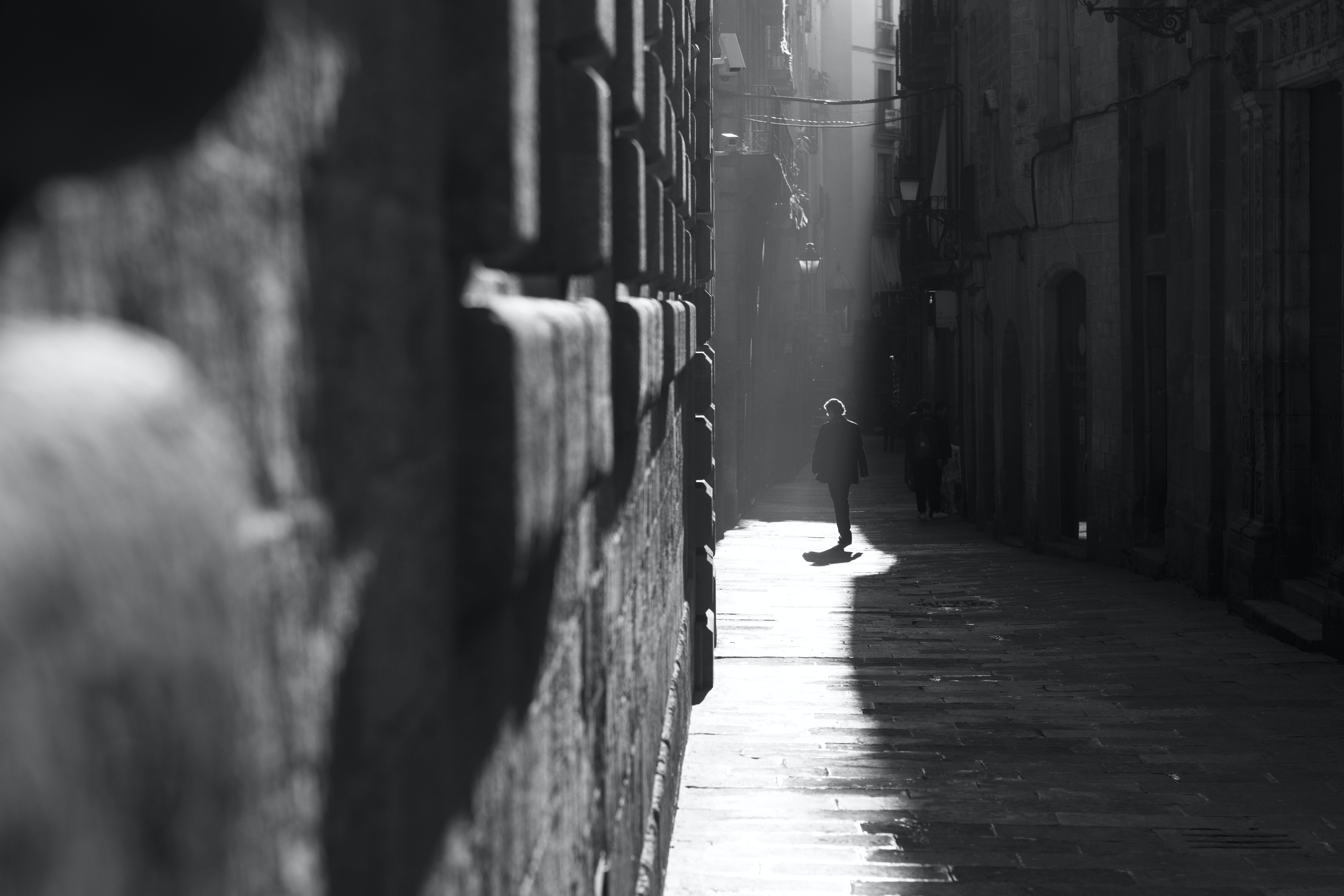 Person Walking in Alley in Grayscale Photography