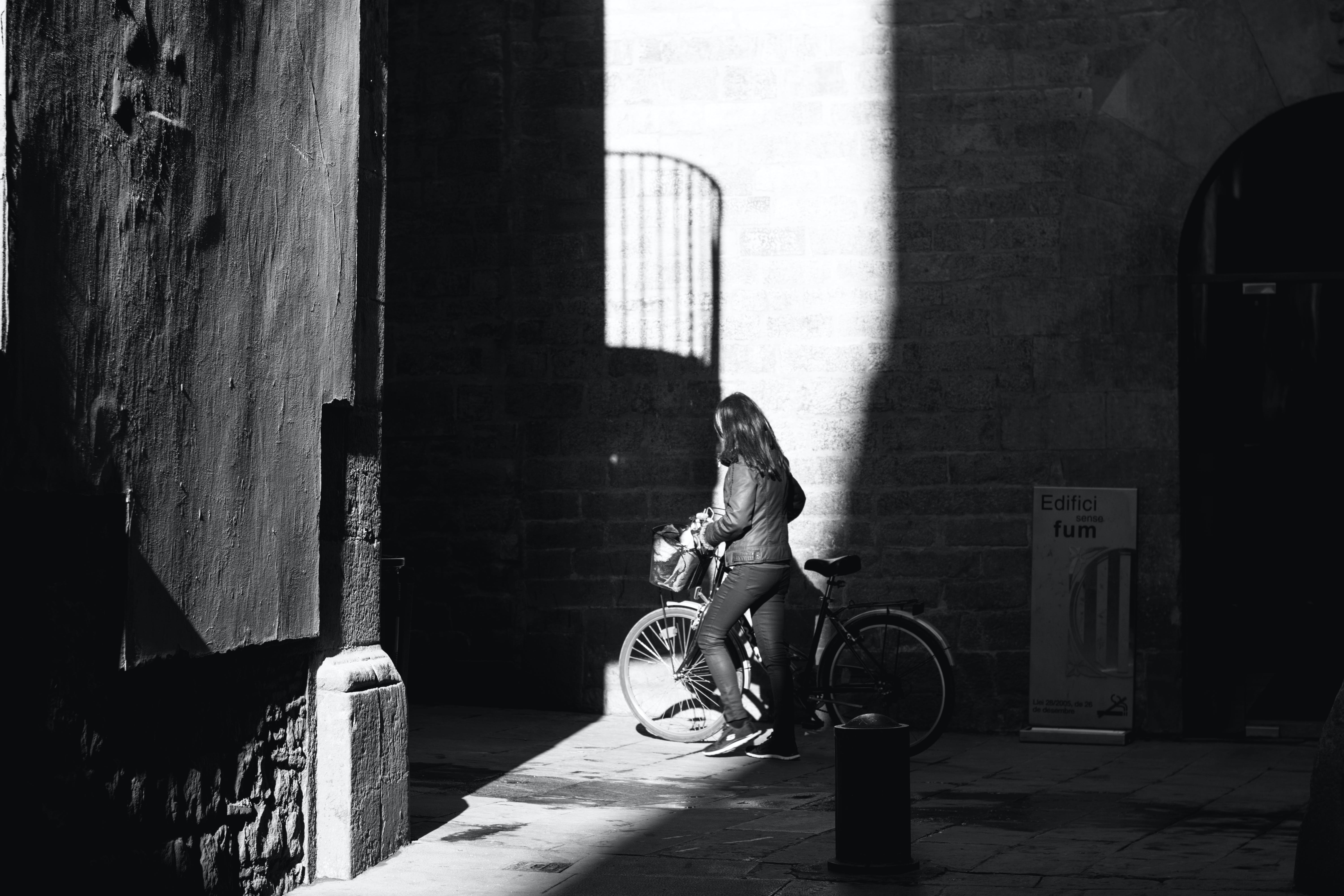 Grayscale Photo of Woman with Her Bicycle