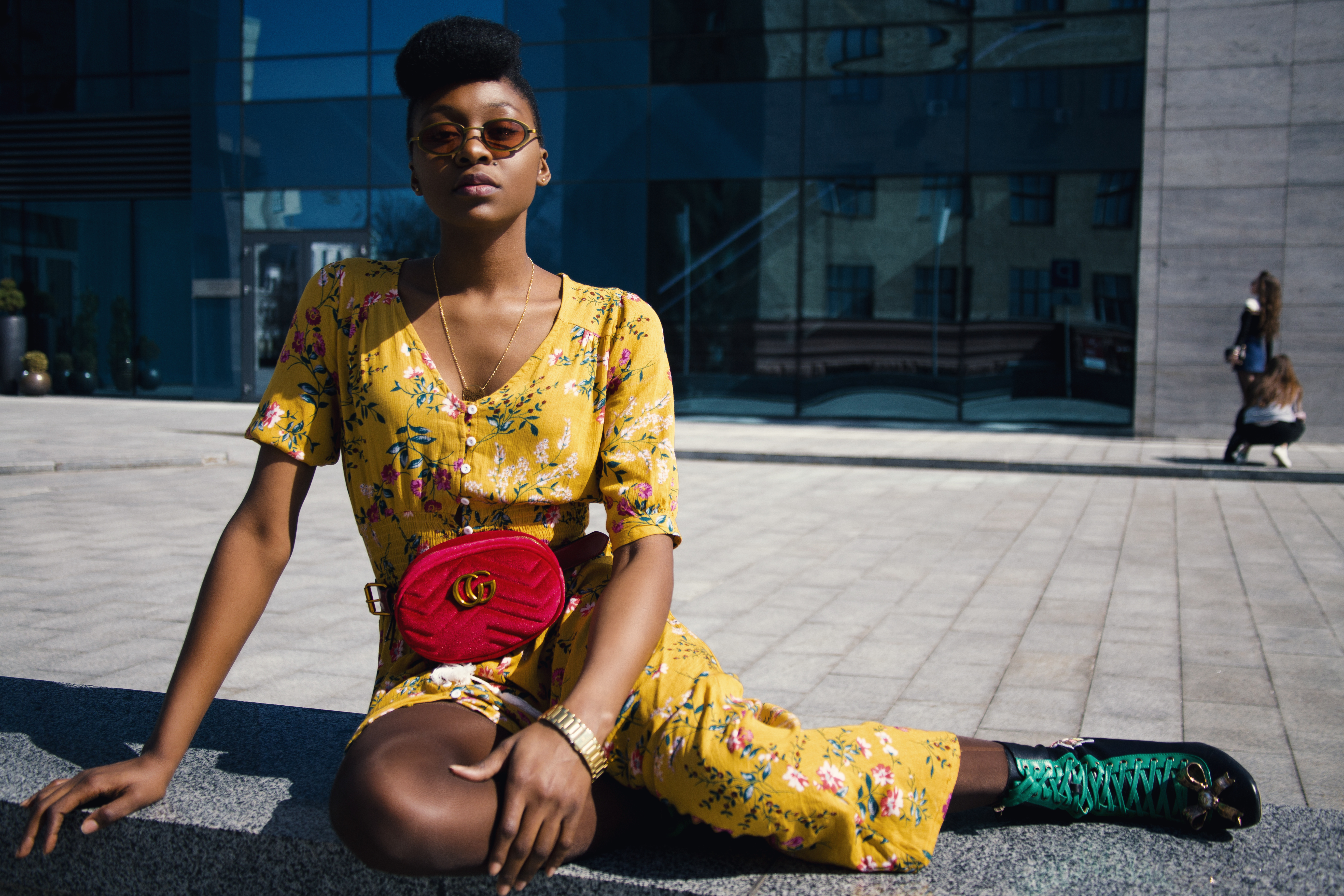 Woman in Yellow Floral Jumpsuit Sitting on Concrete Floor