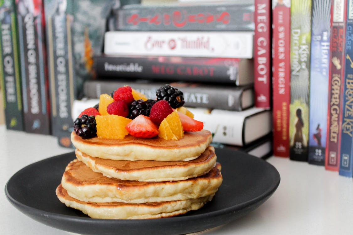 Pancake on Black Plate Near Books