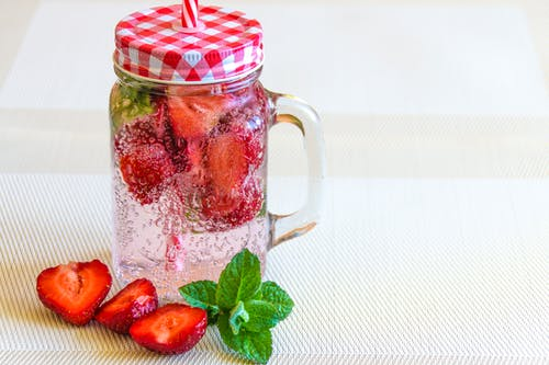 Strawberry Fruits Sliced in Half Near Clear Glass Container