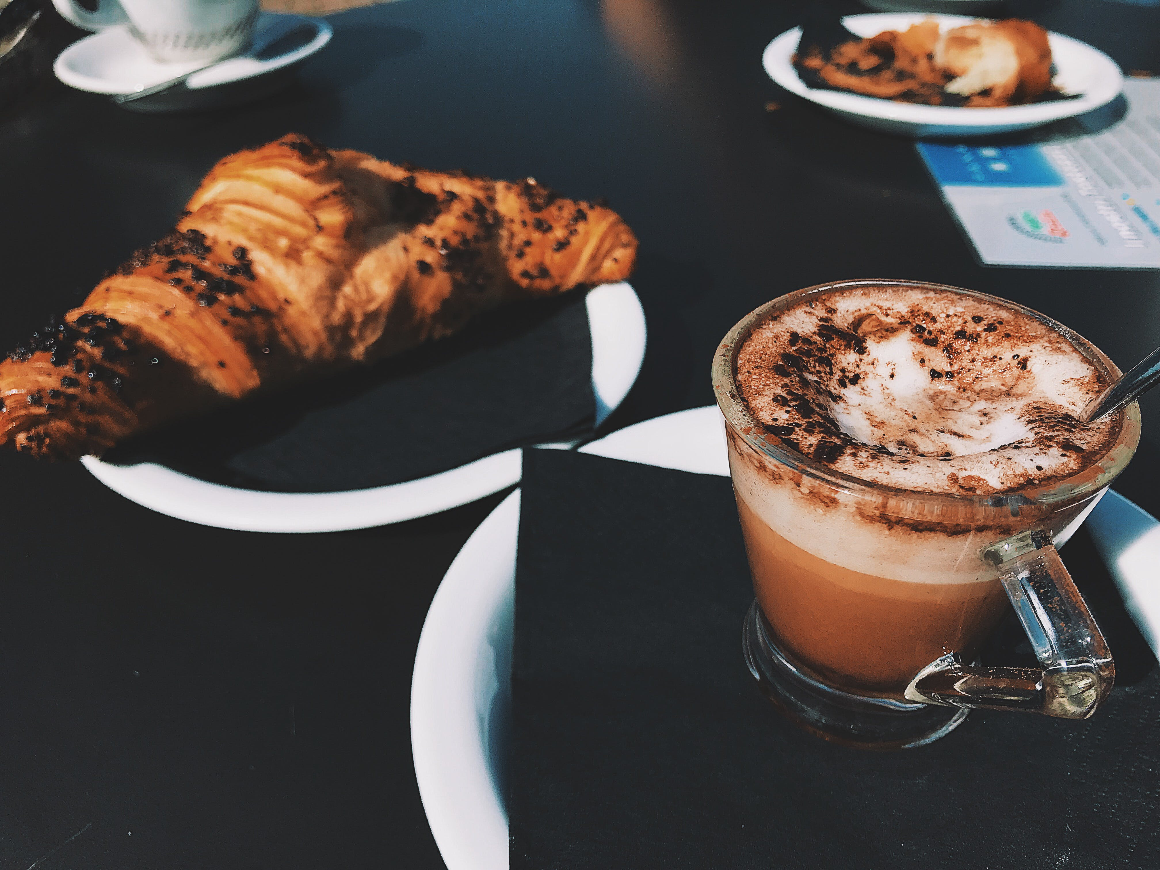 Clear Glass Cup Filled With Cappuccino Beside Croissant Bread