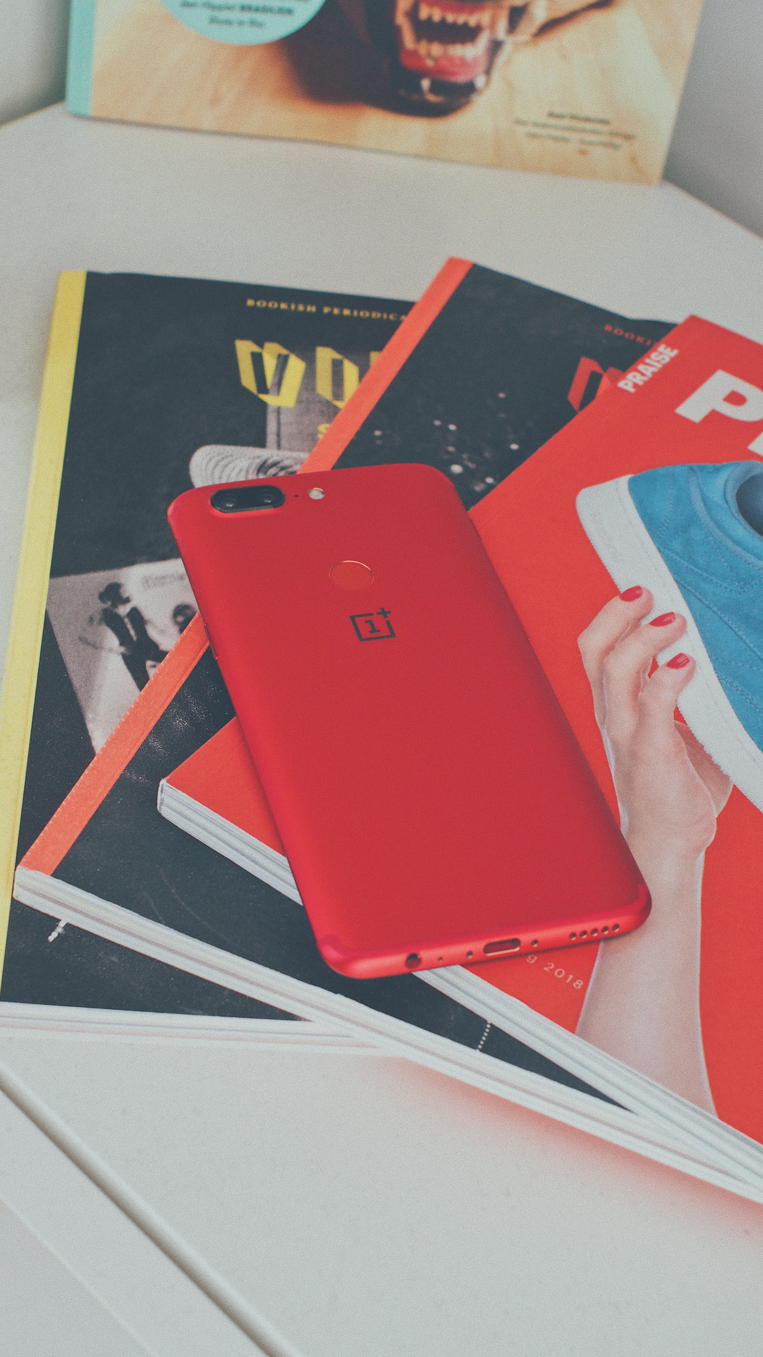 Red Oneplus Smartphone on Books