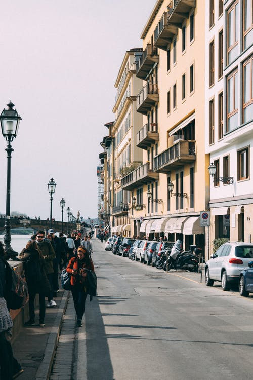 People Walking Along Pavement Near Building