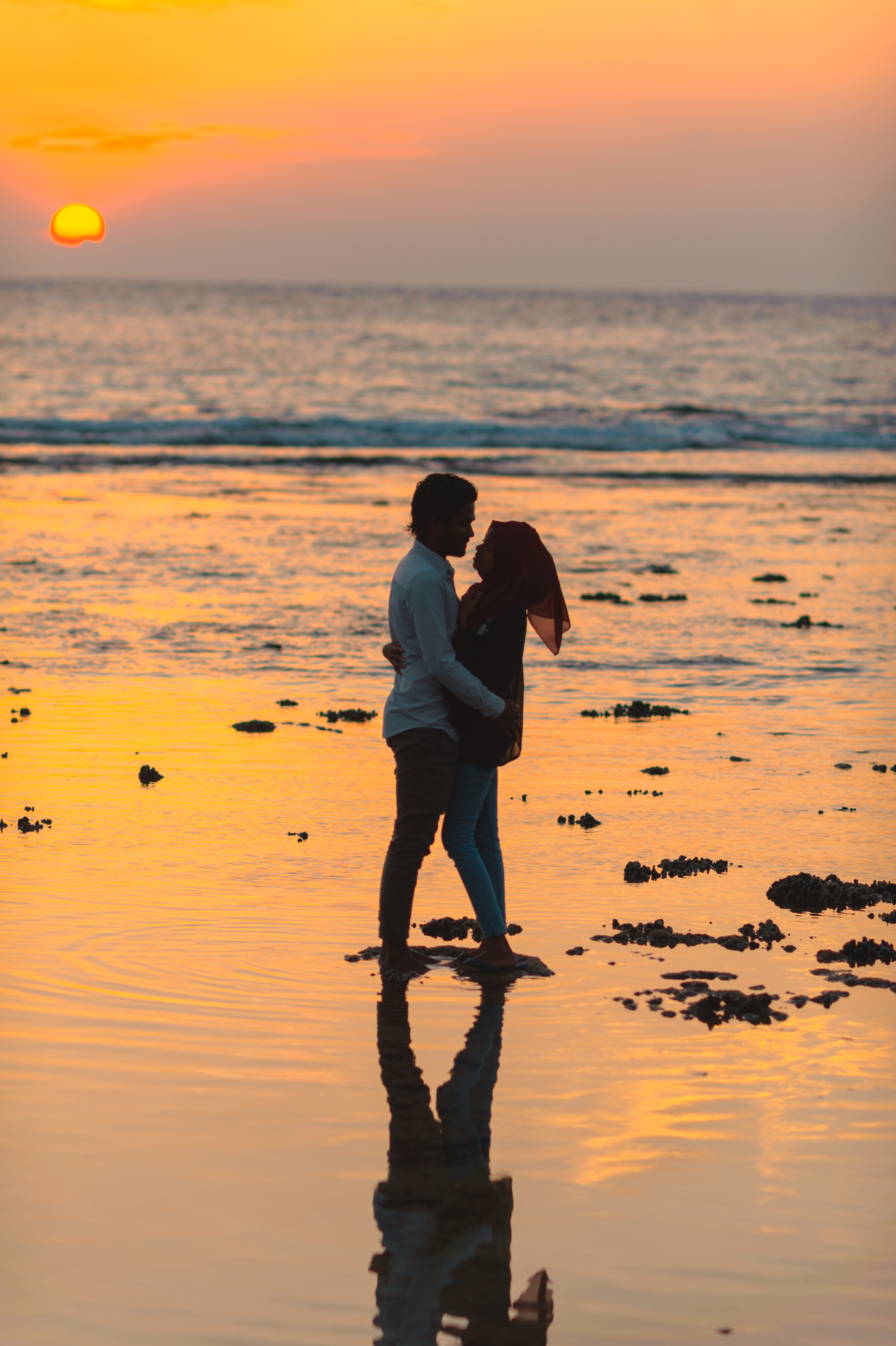 Man and Woman Hugging by the Seashore during Sunset