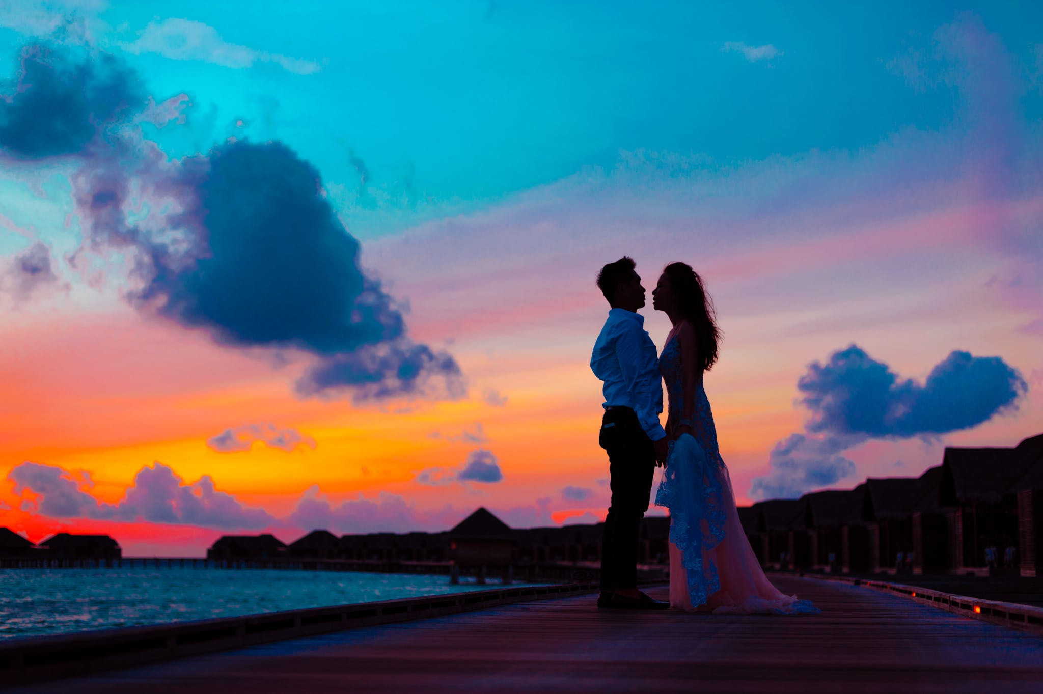 Man and Woman Wearing Wedding Attire Standing on Sea Dock during Golden Hour